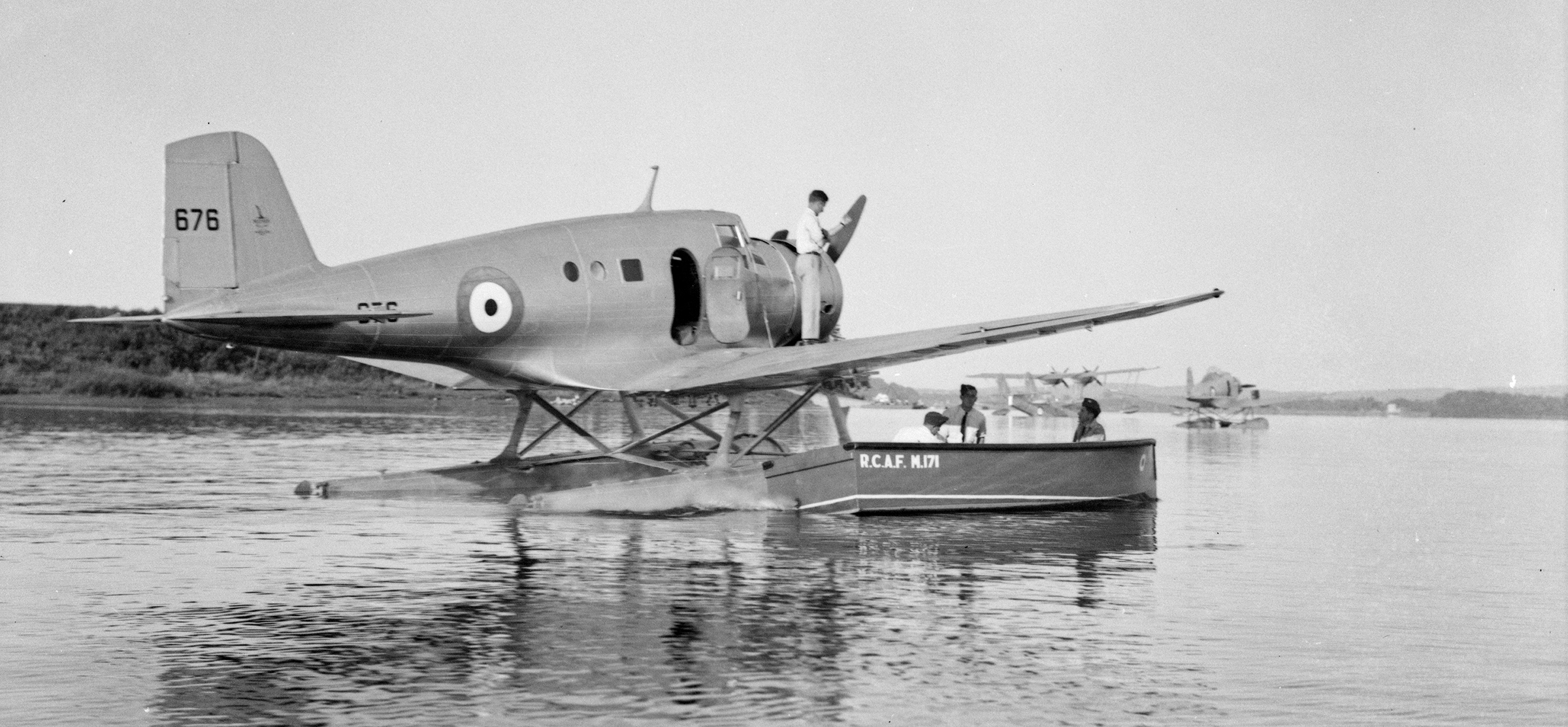 Supplies are loaded onto the RCAF's Northrop Delta No. 676 from 8 Squadron in preparation for a flight from Rockcliffe, Ontario, to Sydney, Nova Scotia, on August 26, 1939. Note the powered launch belonging to the RCAF Marine Service. PHOTO: DND, PA-063532