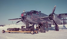 "At the Royal Canadian Air Force station in Goose Bay, Labrador, ammunition is loaded on a Mitchell aircraft. This medium-sized B-25 bomber from 406 Squadron ""City of Saskatoon"" was deployed to participate in Exercise Sun Dog III. The Royal Canadian Air Force and the Canadian Army took part in this joint exercise which took place in the Labrador-Ungava region from February 4 to 14, 1952. PHOTO: PC-75, DND Archives"