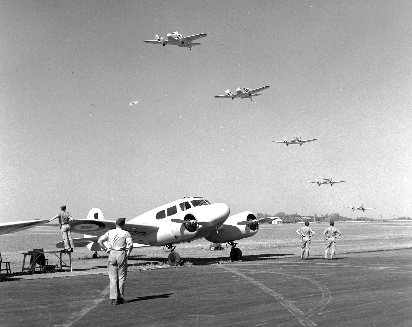 In perfect formation, five Cessna Cranes of the Royal Canadian Air Force fly over their airfield, where one Crane rests on the ground, during training on July 19, 1941. These twin-engine planes are used to train bomber pilots for their overseas jobs against the Axis. PHOTO: DND Archives, PL-5747