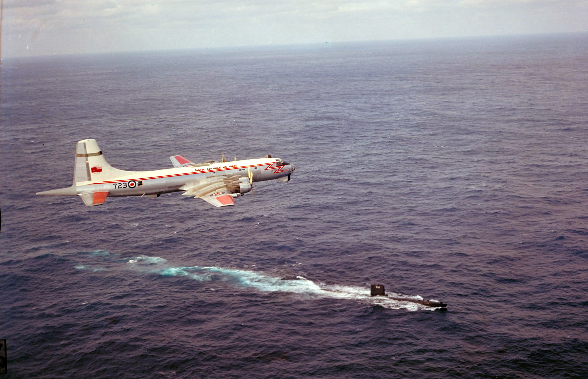 A CP-107 Argus flies over a submarine in the Atlantic Ocean. PHOTO: DND Archives, PCN-733