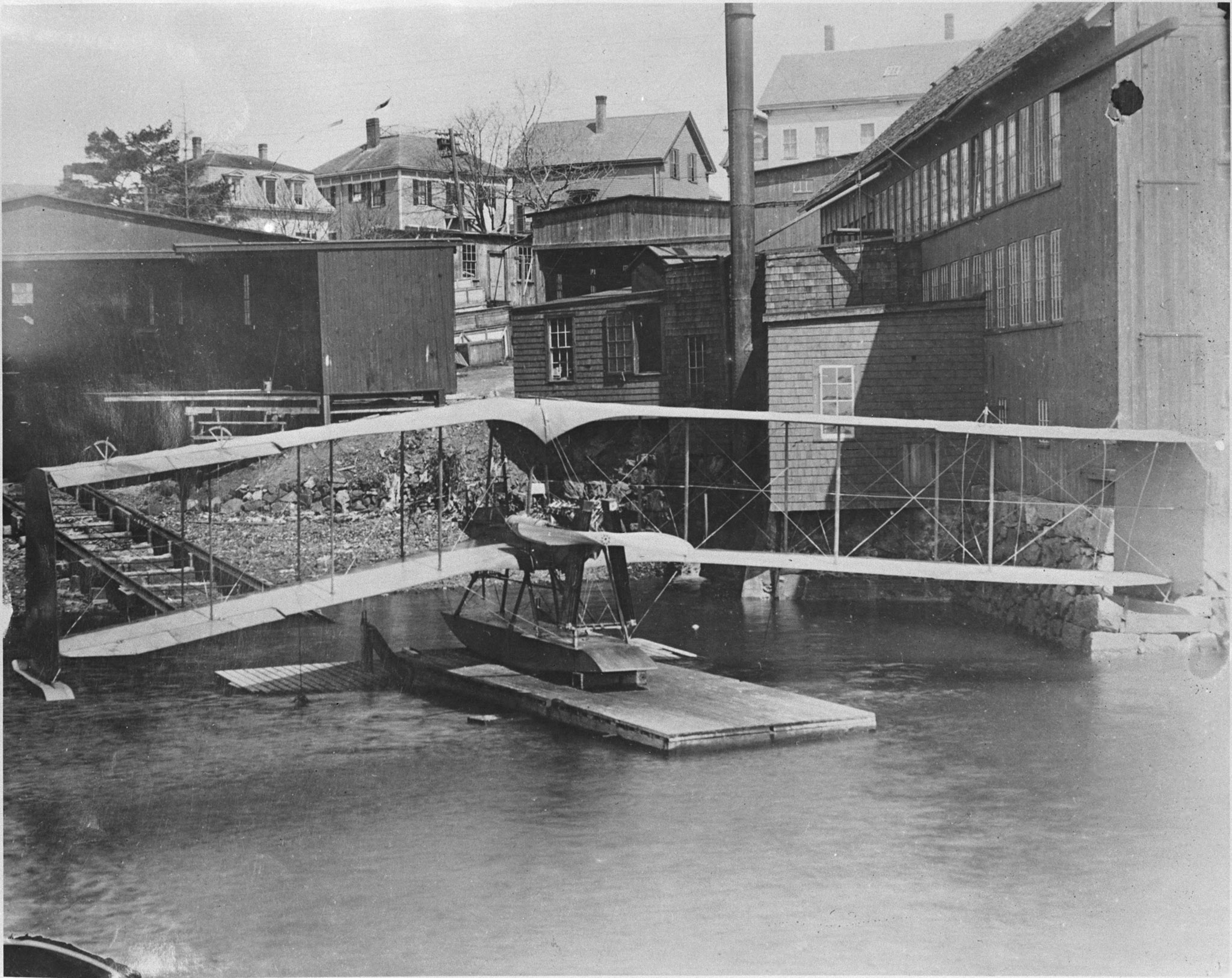 The Burgess-Dunne floatplane, Canada's first military aircraft, rests on a floating dock. PHOTO: DND Archives, PL-115112