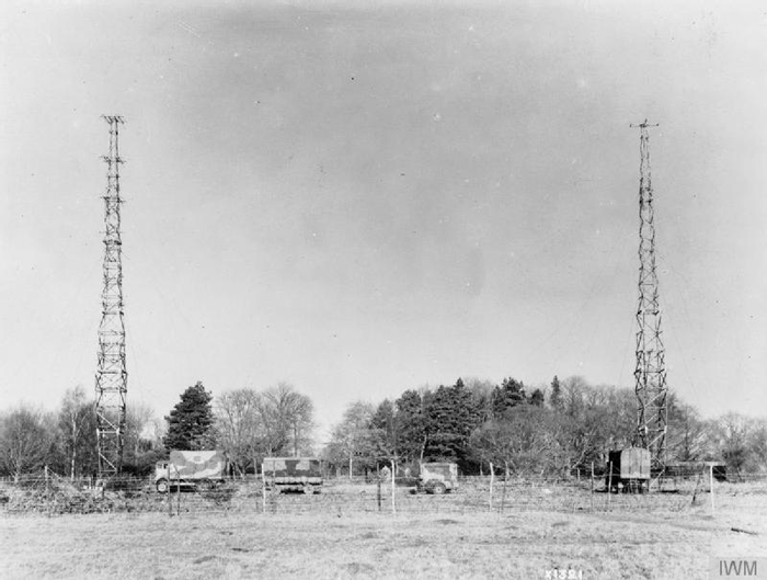 Figure 1 shows two portable radar towers erected approximately 25 metres apart. The transmitting mast is on the left and the receiving mast on the right. Parked in the space between the towers are several signal-processing vehicles. End Figure 1.