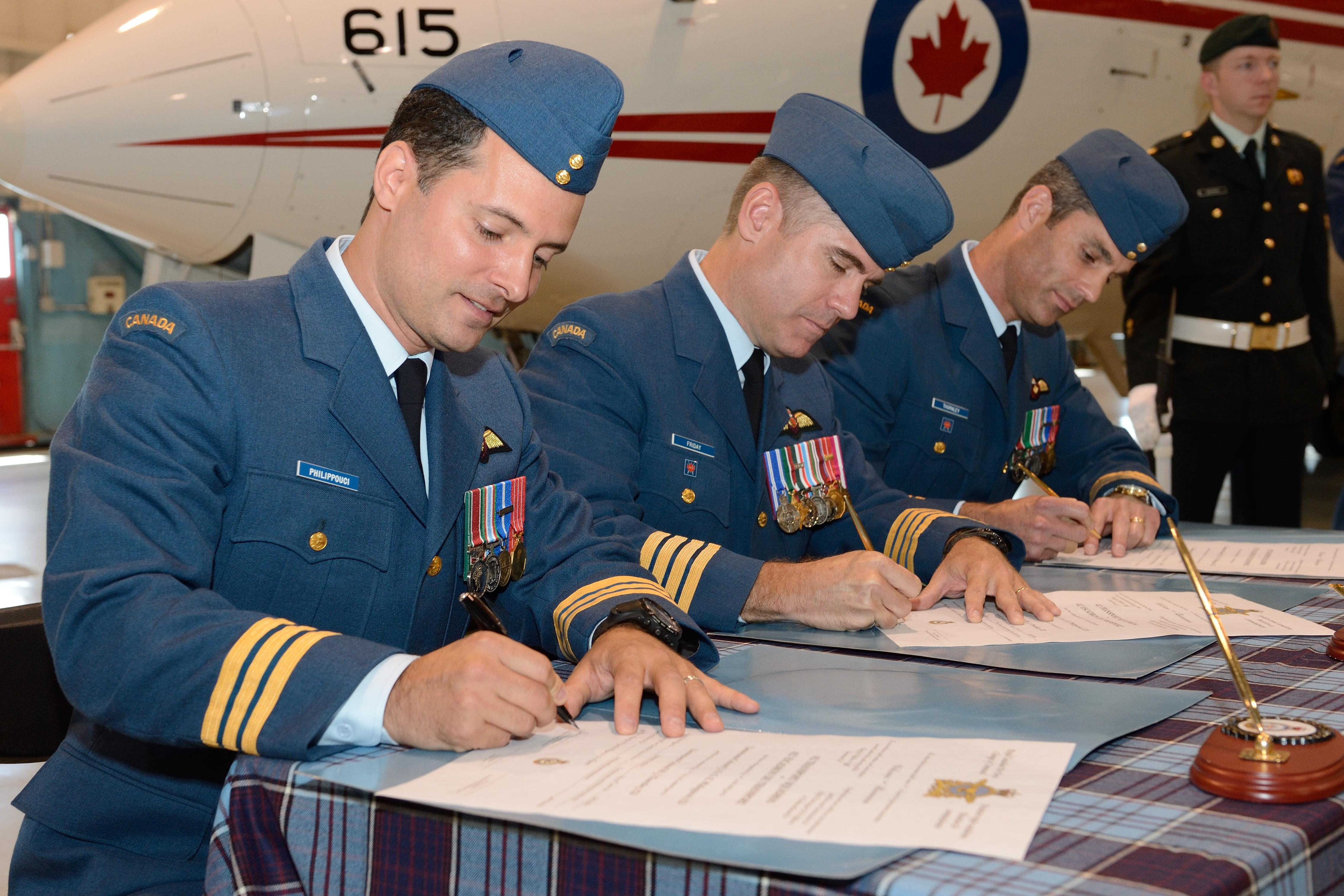 Signing of the official scroll recording the Change of Command by Col Sean Friday, LCol Michael Thornley, and LCol Éric Philippouci.