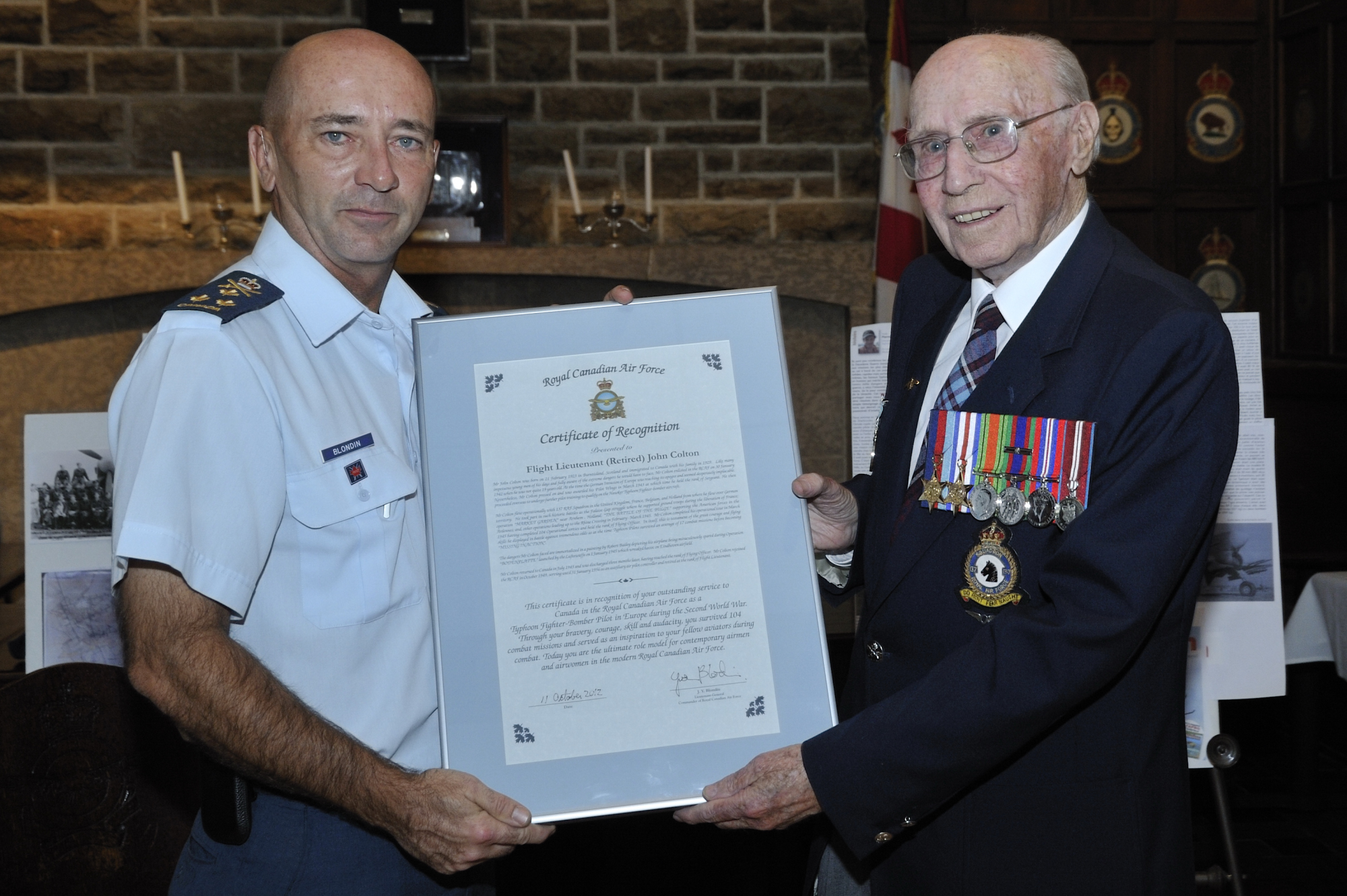 "From fighter pilot to fighter pilot: Lieutenant-General Yvan Blondin presents a Royal Canadian Air Force certificate of recognition to Flight Lieutenant John Colton in recognition of his ""outstanding service to Canada in the Royal Canadian Air Force…during the Second World War"". PHOTO: Sergeant Paz Quillé."