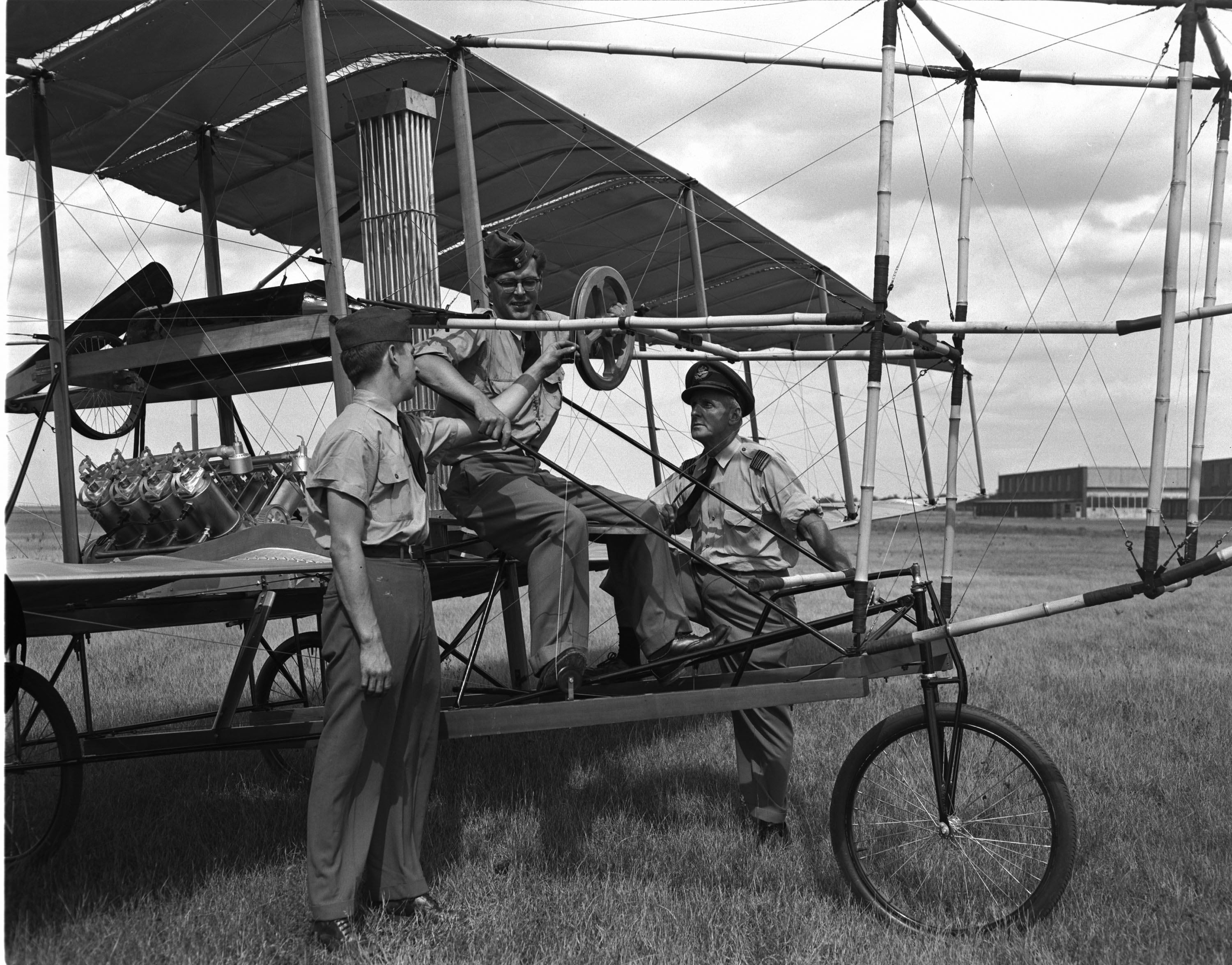 Leading Aircraftman Lionel McCaffery sits at the controls of a replica of the Silver Dart that was built to celebrate the 50th anniversary of the first airplane flight in Canada. Standing with the aircraft are Squadron Leader Roy Wood (right) and Leading Aircraftman Mickey Trimm. PHOTO: PL-95872, DND Archives