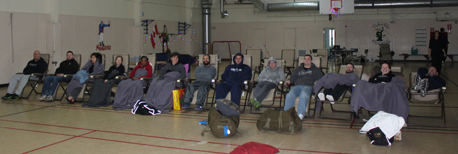 Study subjects were tired but happy after providing saliva samples every two hours for a 24-hour period in CFS Alert's gym. Note the Christmas lights that, along with a projection screen, were the only source of illumination during the 24-hour period. From left to right are Corporal Trevor Hill, Master Seaman Shane Barker, Private Seon Kyu Han, Lieutenant Irina Jakhovets, Corporal Keriean Gairy, Master Corporal Max Mahmodani, Corporal Justin Chamberlain, Corporal Trevor Mclean, Corporal Jason Perrin, Master Corporal Chris Hodge, Lieutenant (Navy) Kaighley Brett and Sergeant Colin Farmer. PHOTO: Brenda Fraser
