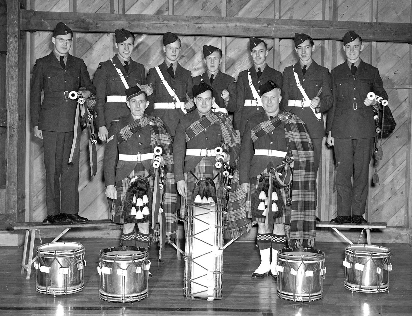 """The young pilots it produces for the Royal Canadian Air Force is one source of pride at No. 9 Service Flying Training School, Centralia, Ont., but the station is also rightly proud of its pipe band. The organization at present comprises five drummers and seven pipers under the direction of Pipe Major, Corporal James Ross of London, Ontario, who has been playing the pipes for 15 years. President of the pipe band is Flying Officer C.A. Finley of Meaford, Ontario, and Warrant Officer Class 1 G.D. Taylor of Toronto is the secretary. In this picture are shown (in the front row from left to right) Pipe Major Corporal J. Ross, London, Ontario; Aircraftman Second Class K.A. Stuebing, Kitchener, Ontario; Aircraftman Second Class W.J. Mutch, Clinton, Ontario; (back row) Aircraftman Second Class L.J. Hutchison, Thamesford, Ontario; Aircraftman Second Class W.S. Stewart, Winnipeg, Aircraftman Second Class J. Graham, Winnipeg,; Aircraftman Second Class A.I. Russell, Winnipeg, Aircraftman Second Class J.S. Gair, Winnipeg,; Leading Aircraftman G. Fairlie, Windsor, Ont.; and Aircraftman Second Class H.A. Forgie, Winnipeg. Missing from the picture are Aircraftman Second Class T.A. Simpson, Winnipeg; and Leading Aircraftman H. Ince, Charlottetown, Prince Edward Island."" PHOTO: DND"