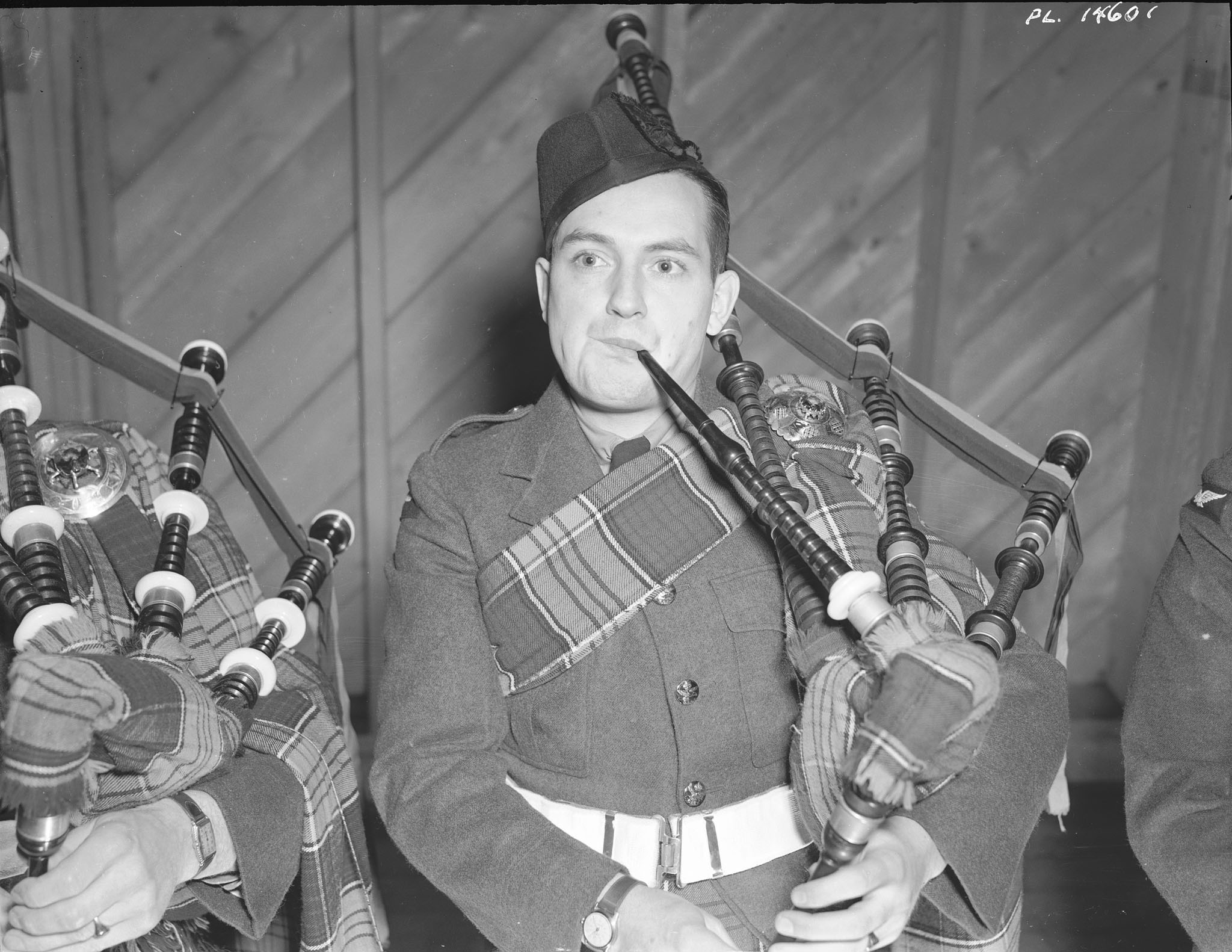 "Aircraftman Second Class K.A. Steubing of Kitchener, Ontario, wearing the new RCAF tartan, warms up his bagpipes on January 14, 1943 at No. 9 Service Flying Training School Centralia in Ontario. The original cutlines reads: ""The band was originally formed at Summerside, Prince Edward Island, but wit"