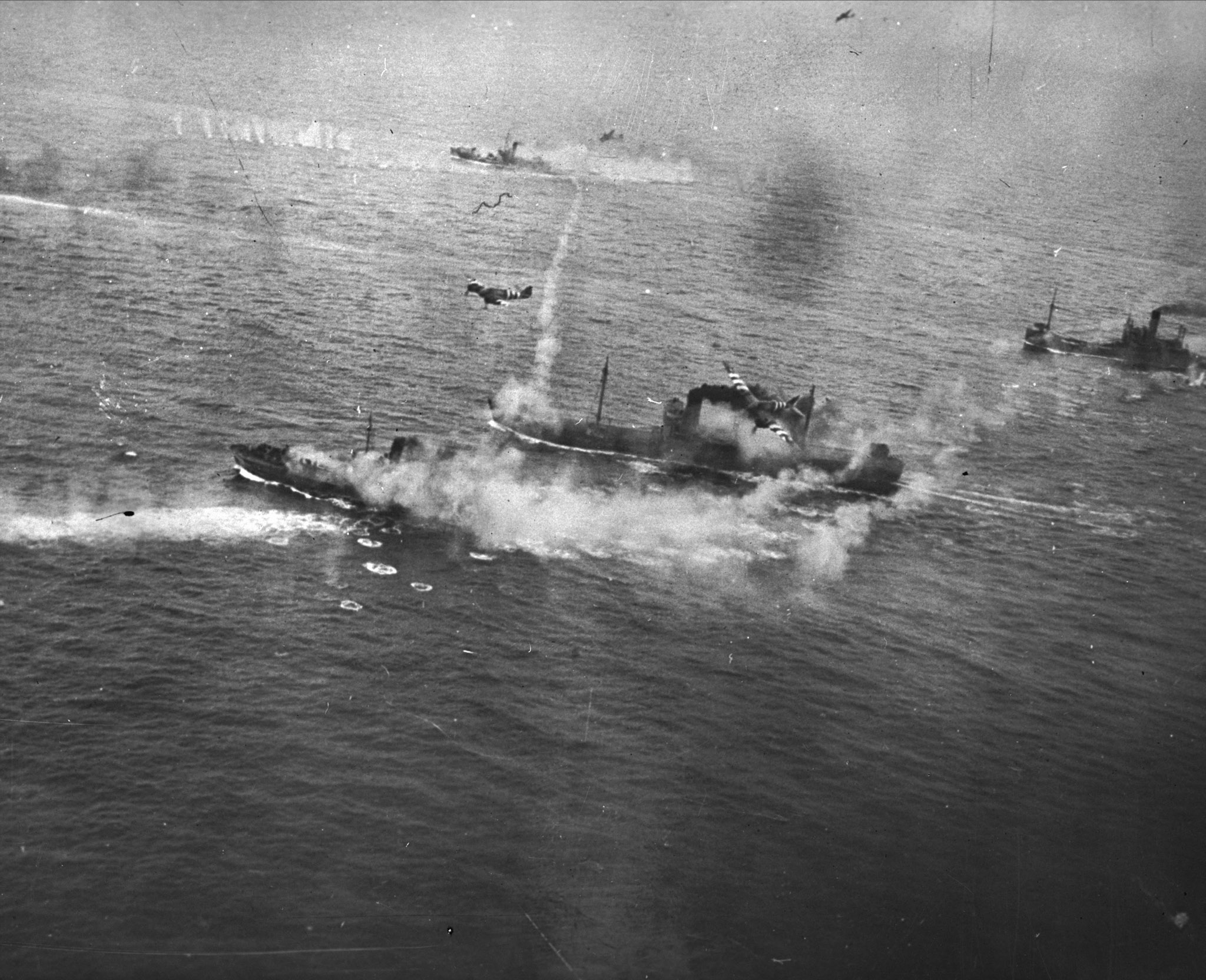 British Beaufighters cripple an enemy convoy off the south coast of Norway. Flying through cloud down to sea level, the Beaufighters from Coastal Command completely surprised the German convoy. In this photo, three armed trawlers and a motor vessel are on fire after a cannon attack by the Beaufighters, which attacked from mast height. PHOTO: DND Archives, PL-61355