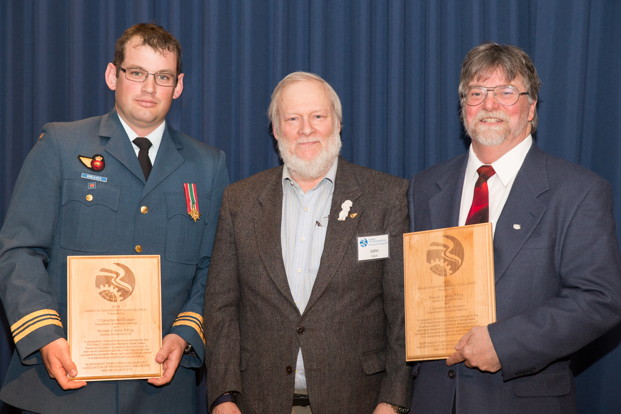 Major Chris Greaves (left) and Mr. Ronald Kent (right), of Stantec Architecture Ltd., accept an Award of Environmental Excellence from Mr. John Clark, of the Northwest Territories and Nunavut Association of Professional Engineers and Geoscientists (NAPEG), on May 15, 2014. The award recognized an in