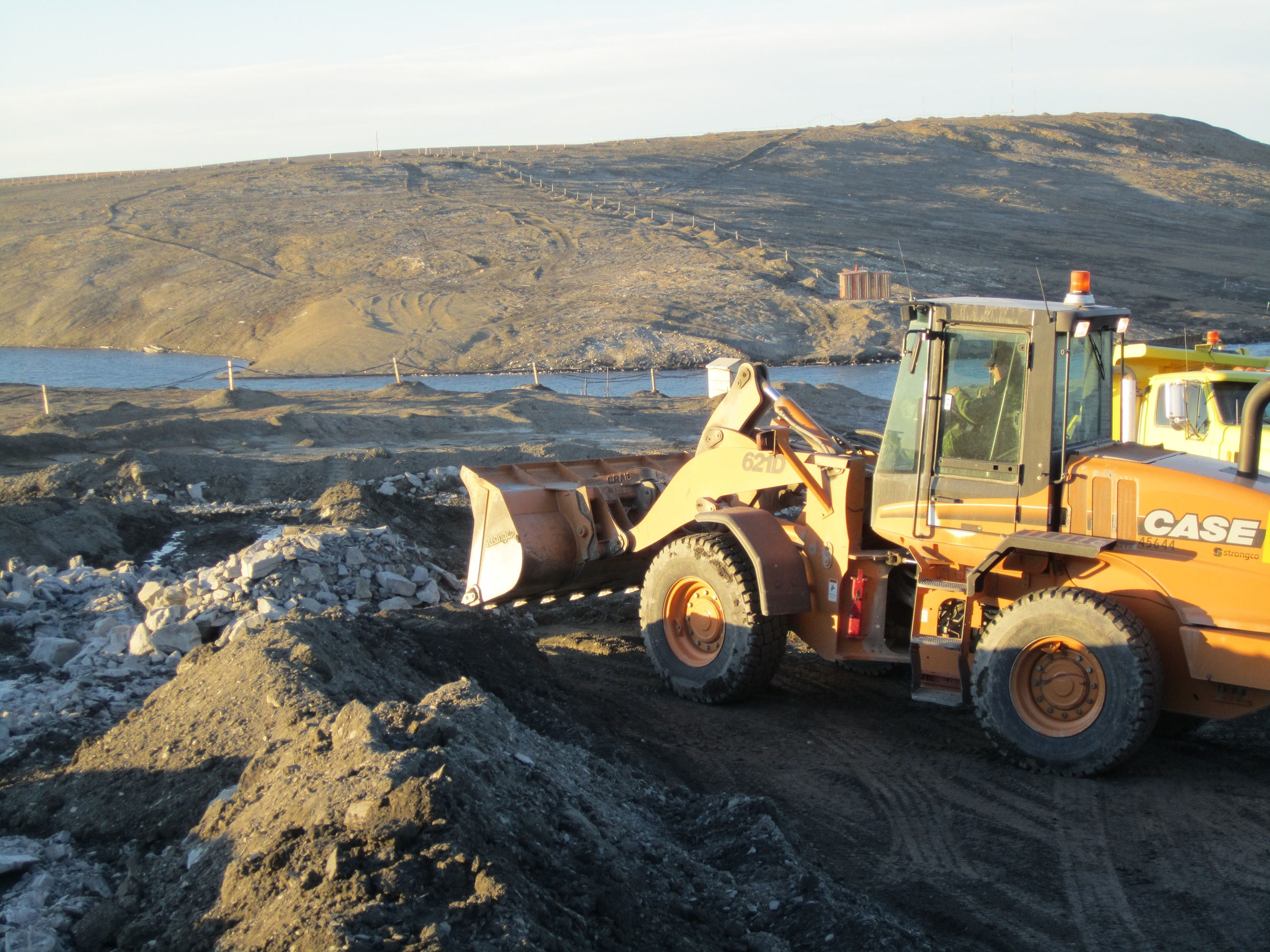 Heavy equipment operated by Corporal Fred Rediker operates an earth mover to place additional granular material that slow and direct the flow of waste water on the hillside. PHOTO: Submitted