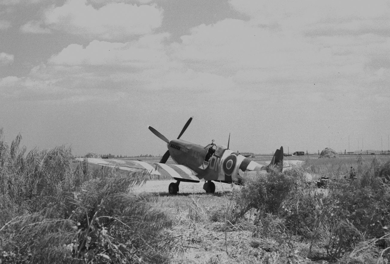 """Nestling in a French wheat field is an RCAF Spitfire [in D-Day markings], which soon may be taken from its pastoral surroundings to go into combat over the enemy lines."" Aircraft that participated in the Normandy invasion were painted in easily recognizable black and white stripes so they would not be confused with enemy aircraft. PHOTO: PL-30299, DND Archives"