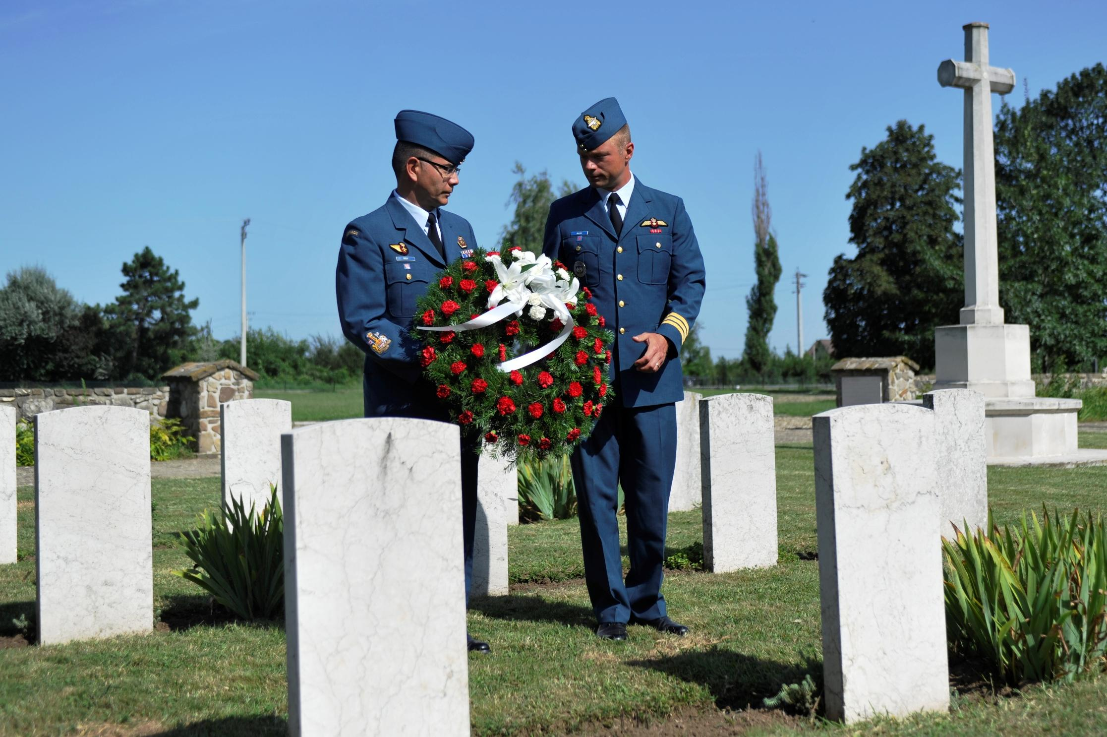The commander of the Canadian Air Task Force Romania, Lieutenant-Colonel David Pletz (right), and Chief Warrant Officer Alain Roy lay a wreath at the Commonwealth War Cemetery in Bucharest on August 1, 2014, in remembrance of the two members of the Royal Canadian Air Force who died in Romania during the Second World War:  Warrant Officer Class I Leslie Frederick Dutton and Flight Sergeant Reginald Thomas White Marsh. PHOTO: Captain Christopher Daniel
