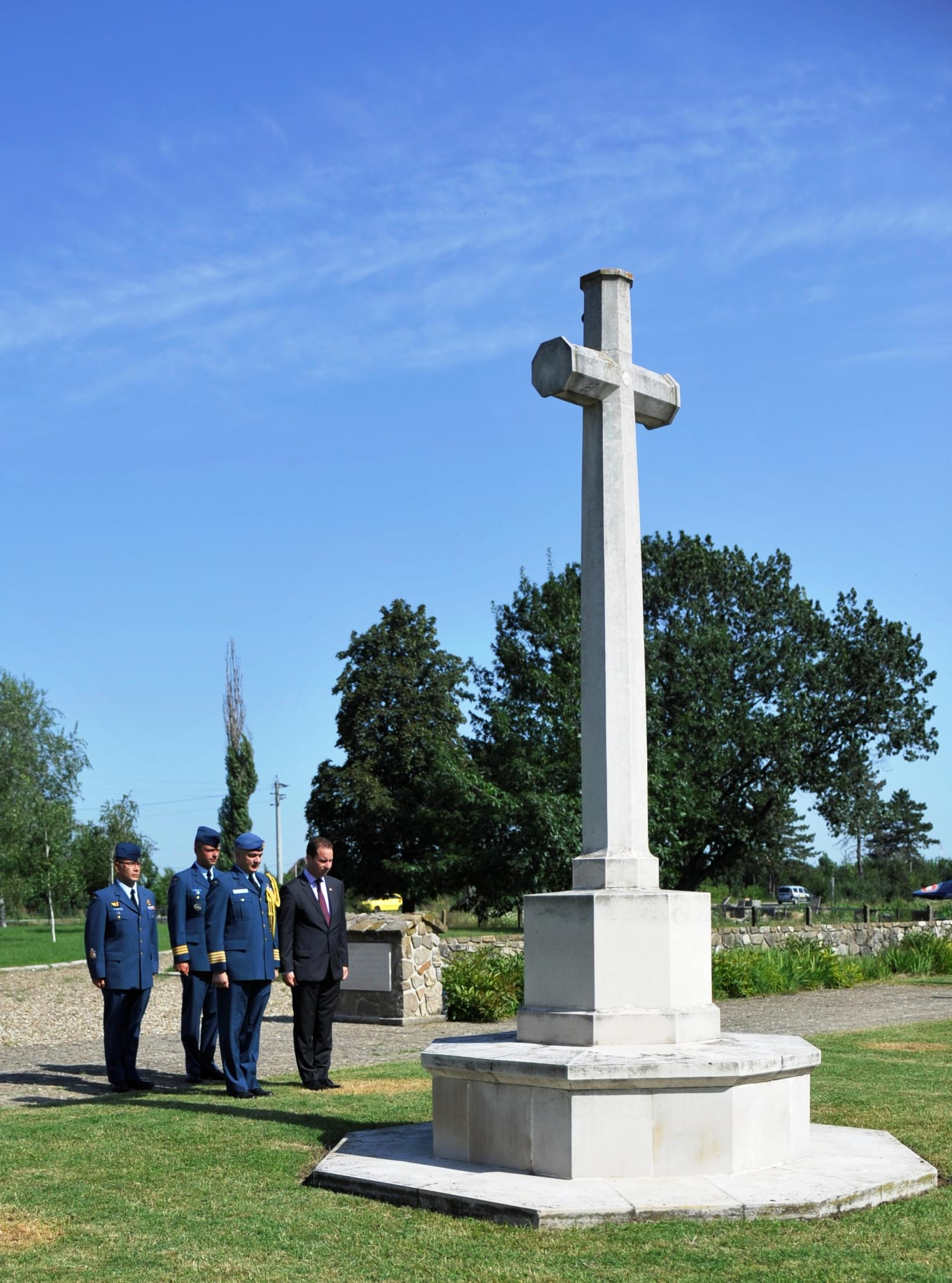 Senior members of the Canadian Air Task Force Romania, the Canadian Defence Attaché and the Chargé d'Affaires of the Canadian Embassy in Bucharest observe a moment of silence at the Commonwealth War Cemetery in Bucharest on August 1, 2014 in remembrance of the two members of the Royal Canadian Air Force who died in Romania during the Second World War:  Warrant Officer Class I Leslie Frederick Dutton and Flight Sergeant Reginald Thomas White Marsh. PHOTO: Captain Christopher Daniel