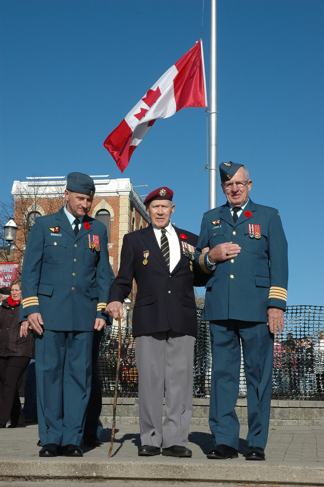 "Lieutenant-Colonel Phil Garbutt (left), commander of 16 Wing Borden, Ontario, Mr. Herb Cloutier (centre), a Second World War veteran, and Honorary Colonel Rob Warman of 16 Wing, prepare to accept the salute from troops ""marching past"" during the 2009 Remembrance Day Ceremony in Barrie, Ontario. PHOTO: Sergeant Kev Parle"