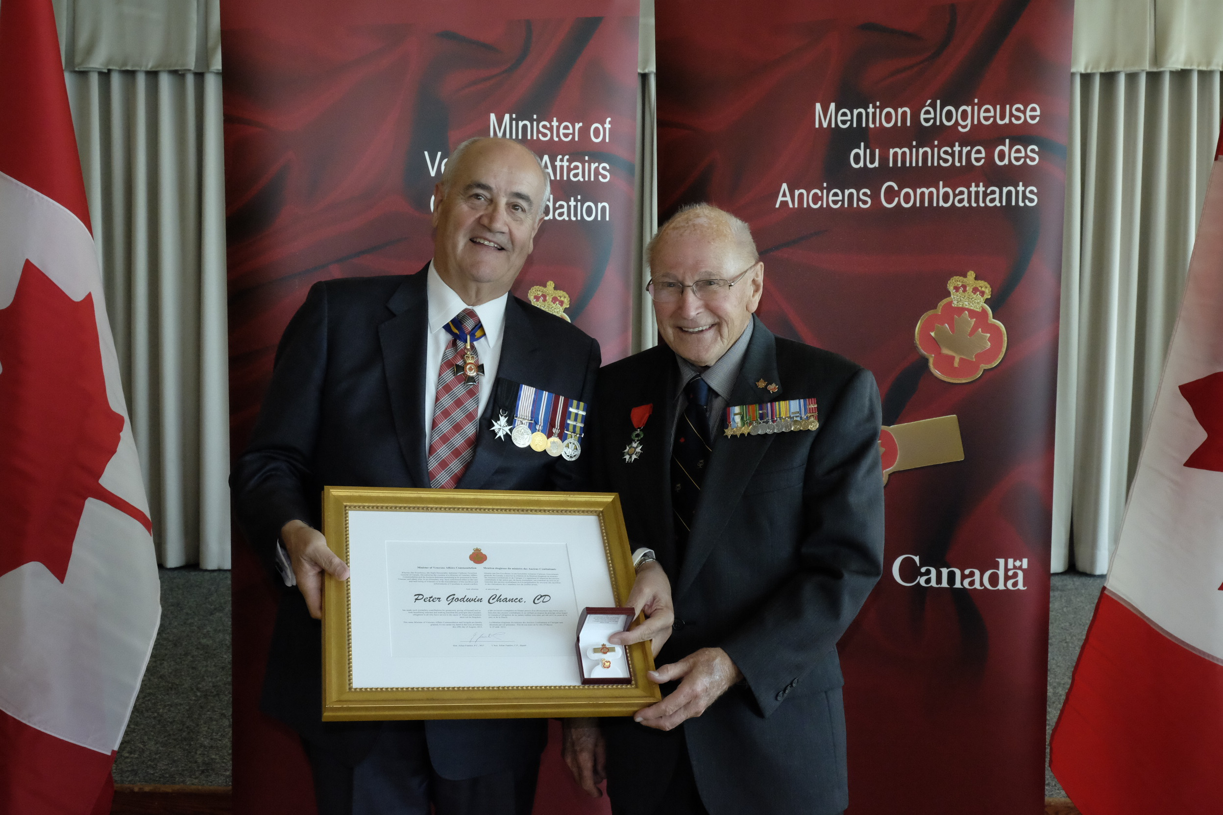 Second World War and Korean War veteran of the Canadian Armed Forces Peter Godwin Chance (right) receives the Minister of Veterans Affairs Commendation from Minister Julian Fantino on September 12, 2014. He recently received the French Legion of Honour Medal at the rank of Knight. He speaks in local schools at Remembrance Day ceremonies, and visits and takes books to geriatric patients in the local hospital, and working with other programs that help veterans. PHOTO: Courtesy of Veterans Affairs Canada