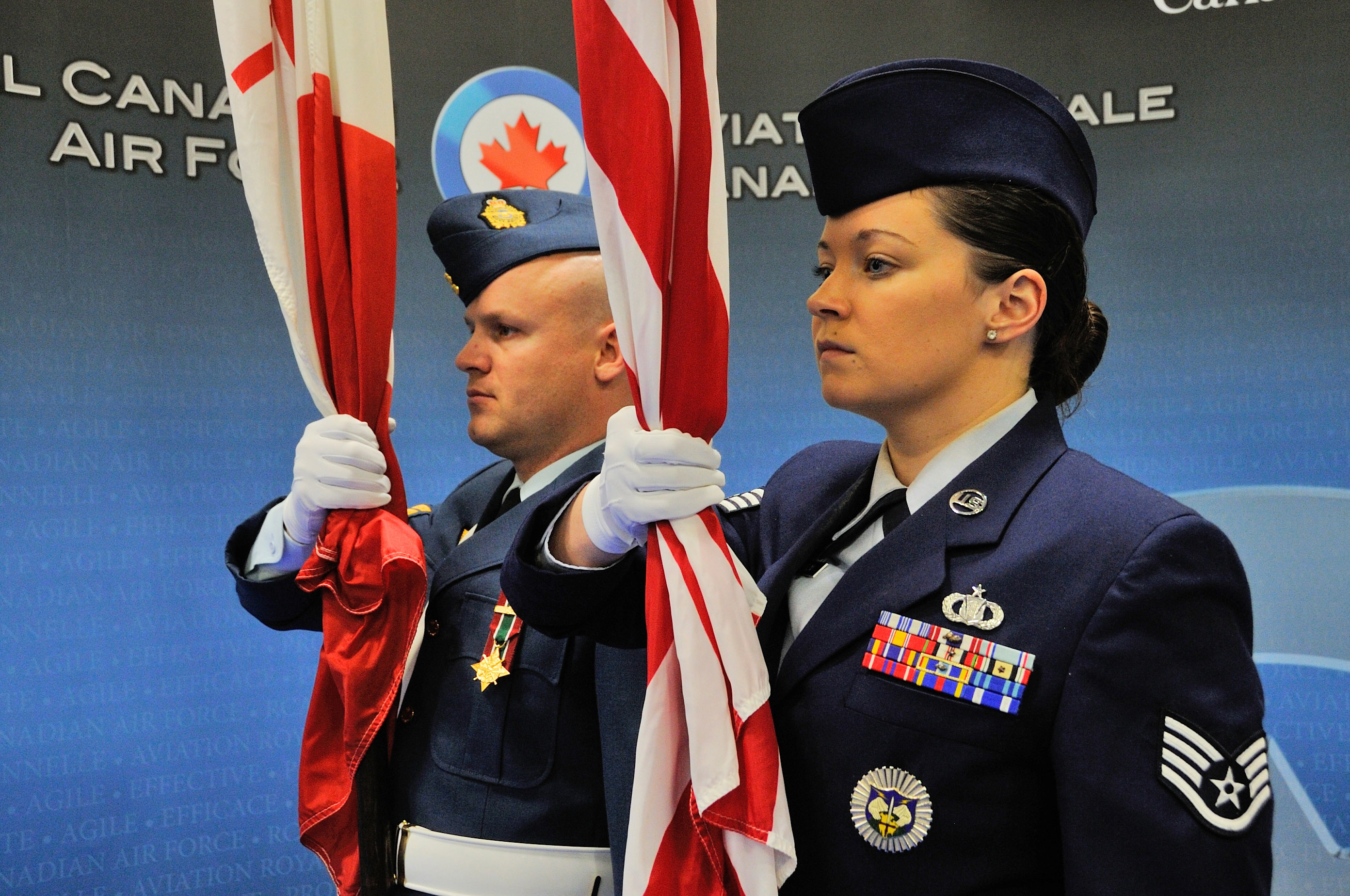 Corporal Christian Eadie (left), Royal Canadian Air Force, and Staff Sergeant Katherine Wilhelm, United States Air Force, act as flag bearers during the National Day of Honour ceremony held in North Bay, Ontario, on May 9, 2014. Both work under the auspices of NORAD.