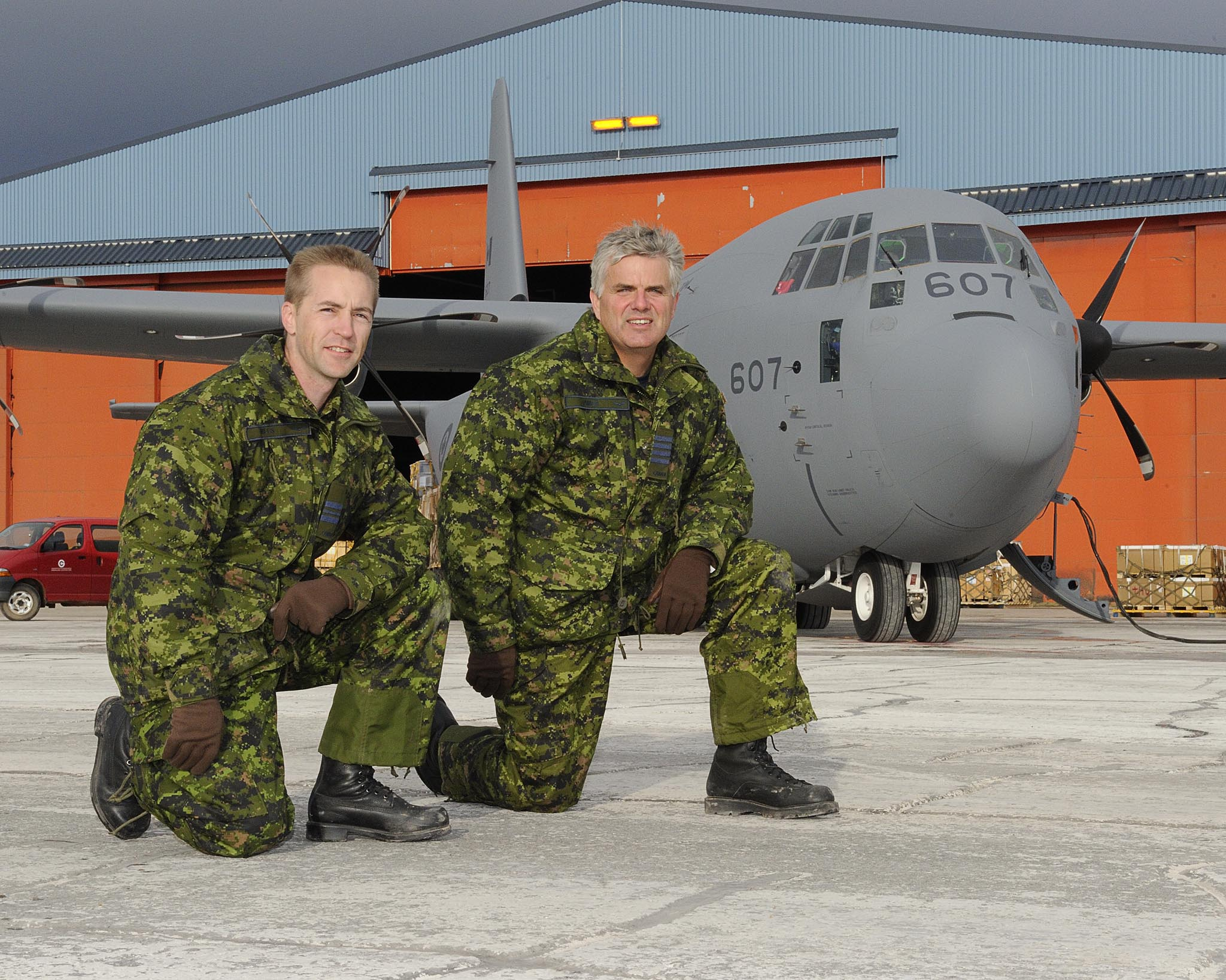 Major Ken Mills, the commanding officer of 2 Air Movements Squadron (left), located at 8 Wing Trenton, Ontario, and the squadron's honorary colonel, Eben James, pose in front of a CC-130J Hercules aircraft in Thule, Greenland, in September 2011 during Operation Boxtop (the semi-annual resupply of Canadian Forces Station Alert in Nunavut). As part of their relationship with their units, honoraries often participate in missions and activities.  PHOTO: Master Corporal Colin Aiken