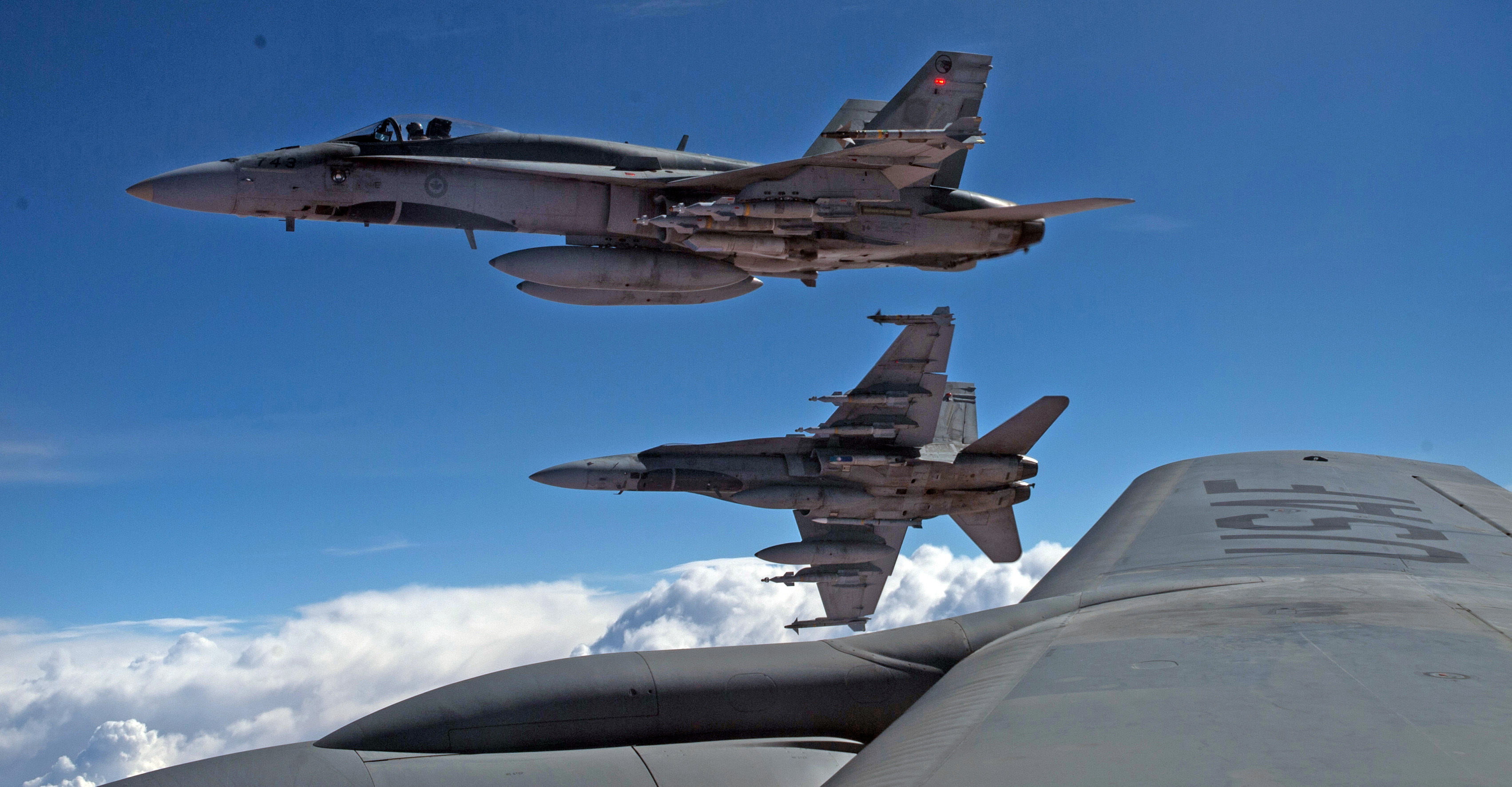 Un KC-135 Stratotanker des États-Unis, affecté à 340th Expeditionary Air Refueling Squadron, ravitaille des CF-188 Hornet de l'Aviation royale canadienne le 30 Octobre 2014. PHOTO: United States Air Force