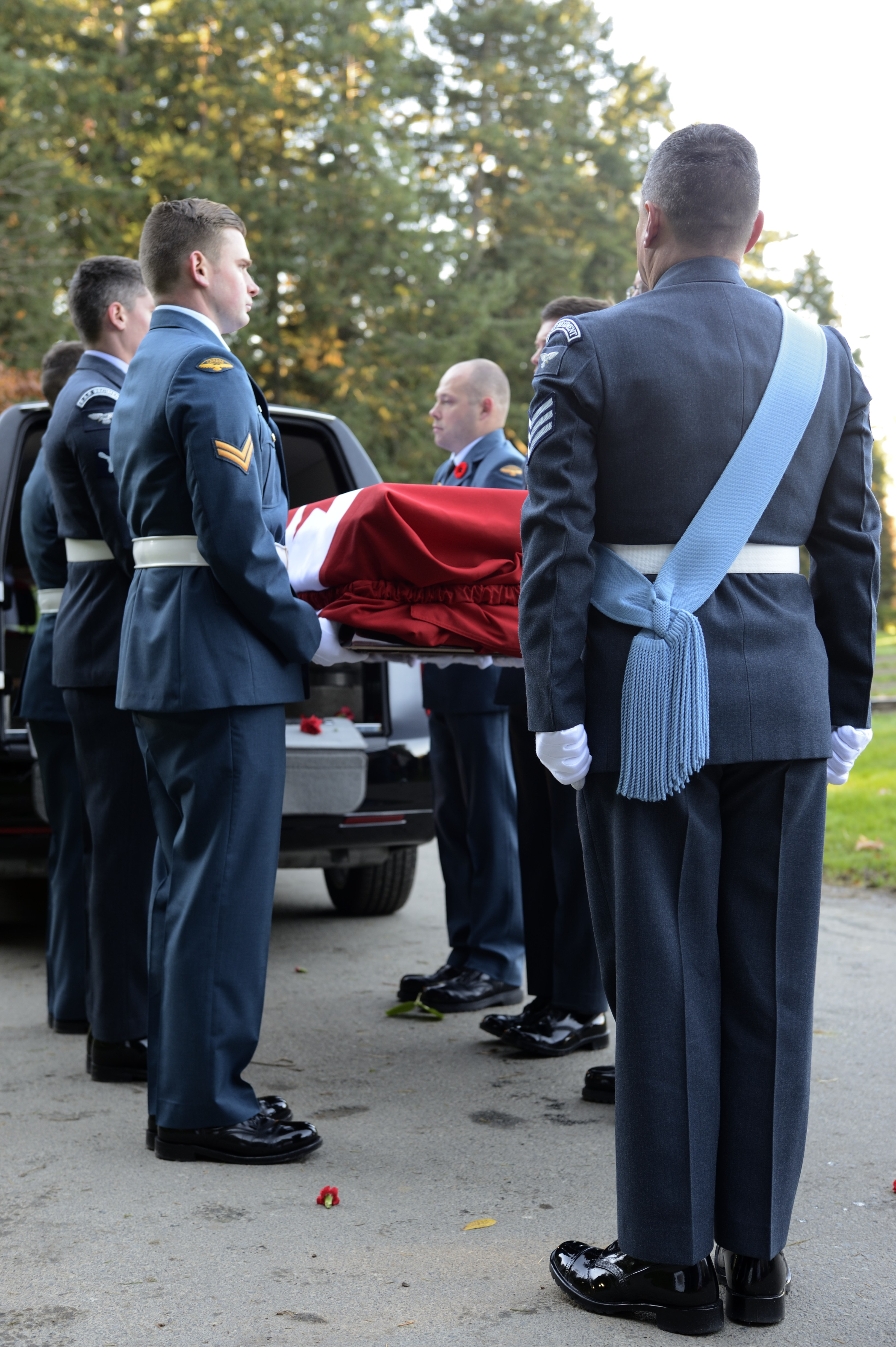 During a November 10, 2014, interment service at Royal Oak Burial Park in Victoria, British Columbia, Royal Canadian Air Force (RCAF) pallbearers accept the casket containing the remains of Avro Anson flight L7056 crewmen Pilot Officer Charles George Fox, Pilot Officer Anthony William Lawrence and Sergeant Robert Ernest Luckock, of the Royal Air Force (RAF), and RCAF Sergeant William Baird. The airmen were lost when their aircraft disappeared over Vancouver Island, British Columbia, on October 30, 1942. PHOTO: Corporal Malcolm Byers