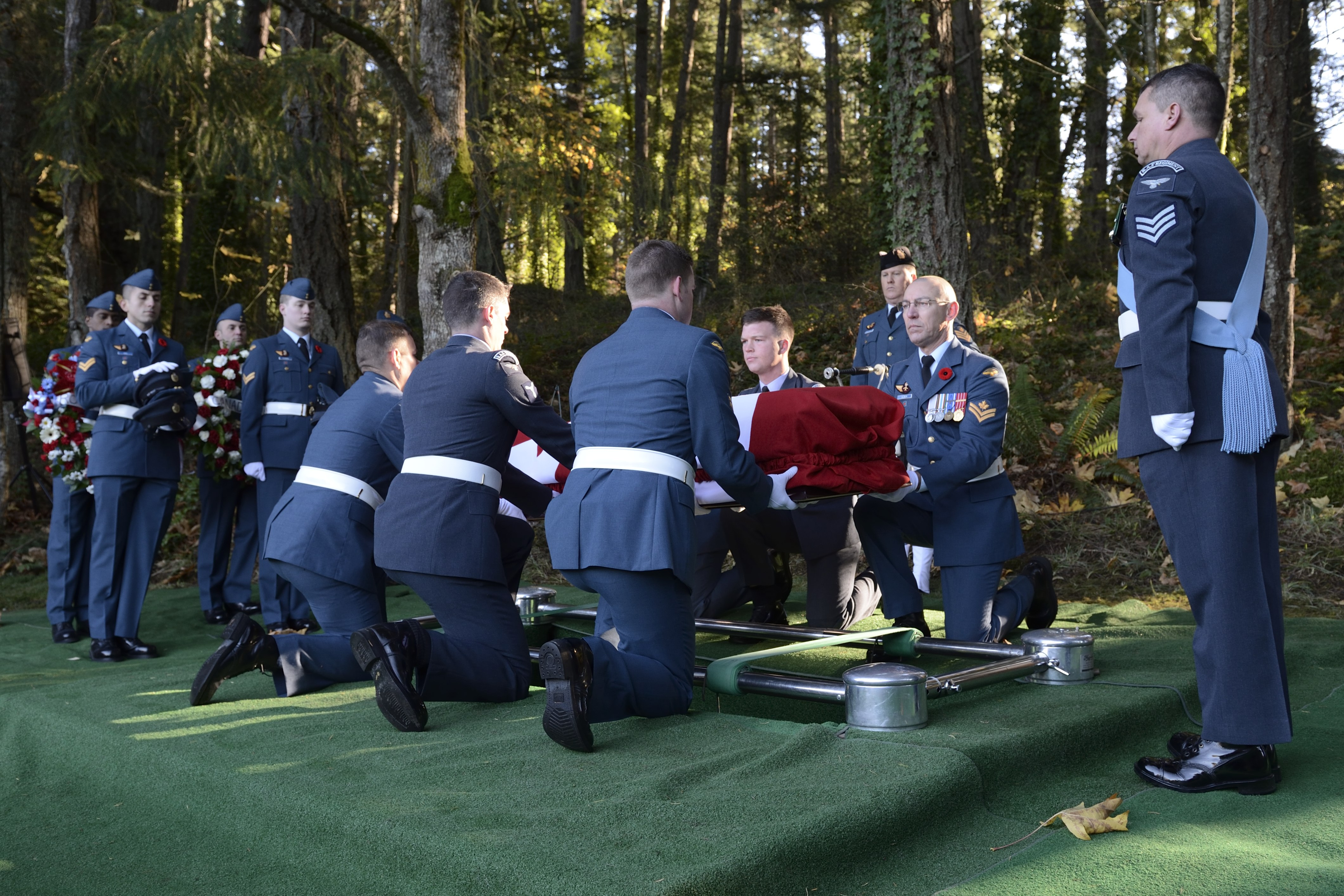 On November 10, 2014, Royal Canadian Air Force (RCAF) pall bearers place the casket of Pilot Officer Charles George Fox, Pilot Officer Anthony William Lawrence and Sergeant Robert Ernest Luckock, of the Royal Air Force, and Sergeant William Baird, of the RCAF, at their final resting place in Royal Oak Burial Park in Victoria, British Columbia. PHOTO: Corporal Malcolm Byers