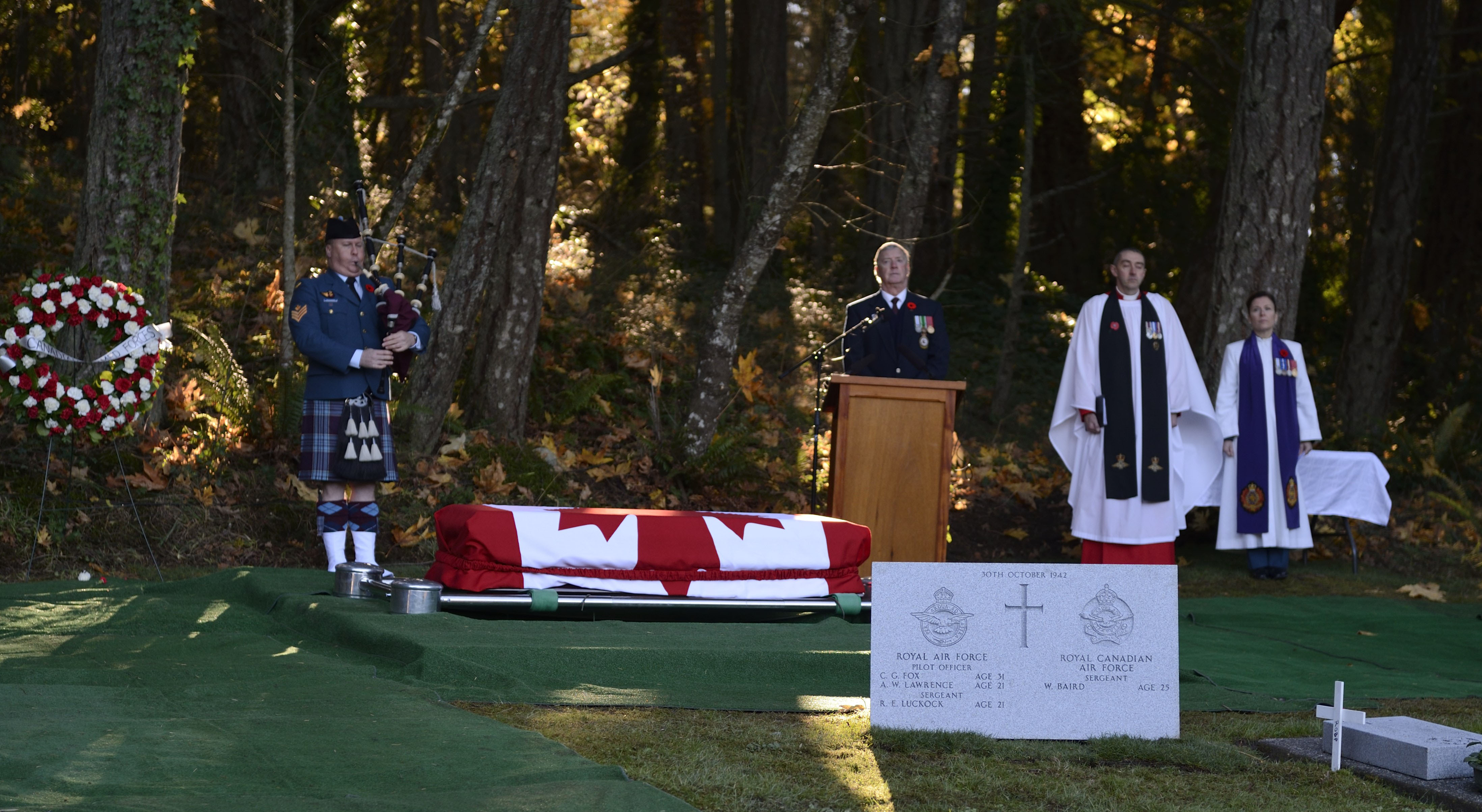 Sunlight illuminates the casket during the November 10, 2014, interment service of Pilot Officer Charles George Fox, Pilot Officer Anthony William Lawrence, and Sergeant Robert Ernest Luckock, of the Royal Air Force (RAF), and Sergeant William Baird, of the Royal Canadian Air Force (RCAF). Captain (Ret) Gary Brown, from the Victoria Branch of the Vancouver Island Aircrew Association (centre, at lectern), RAF Reverend (Group Captain) Nick Barry, and Major Angela James, an RCAF chaplain, listen as RCAF piper Sergeant Alan Buchanan plays the Lament at Royal Oak Burial Park in Victoria, British Columbia. PHOTO: Corporal Malcolm Byers