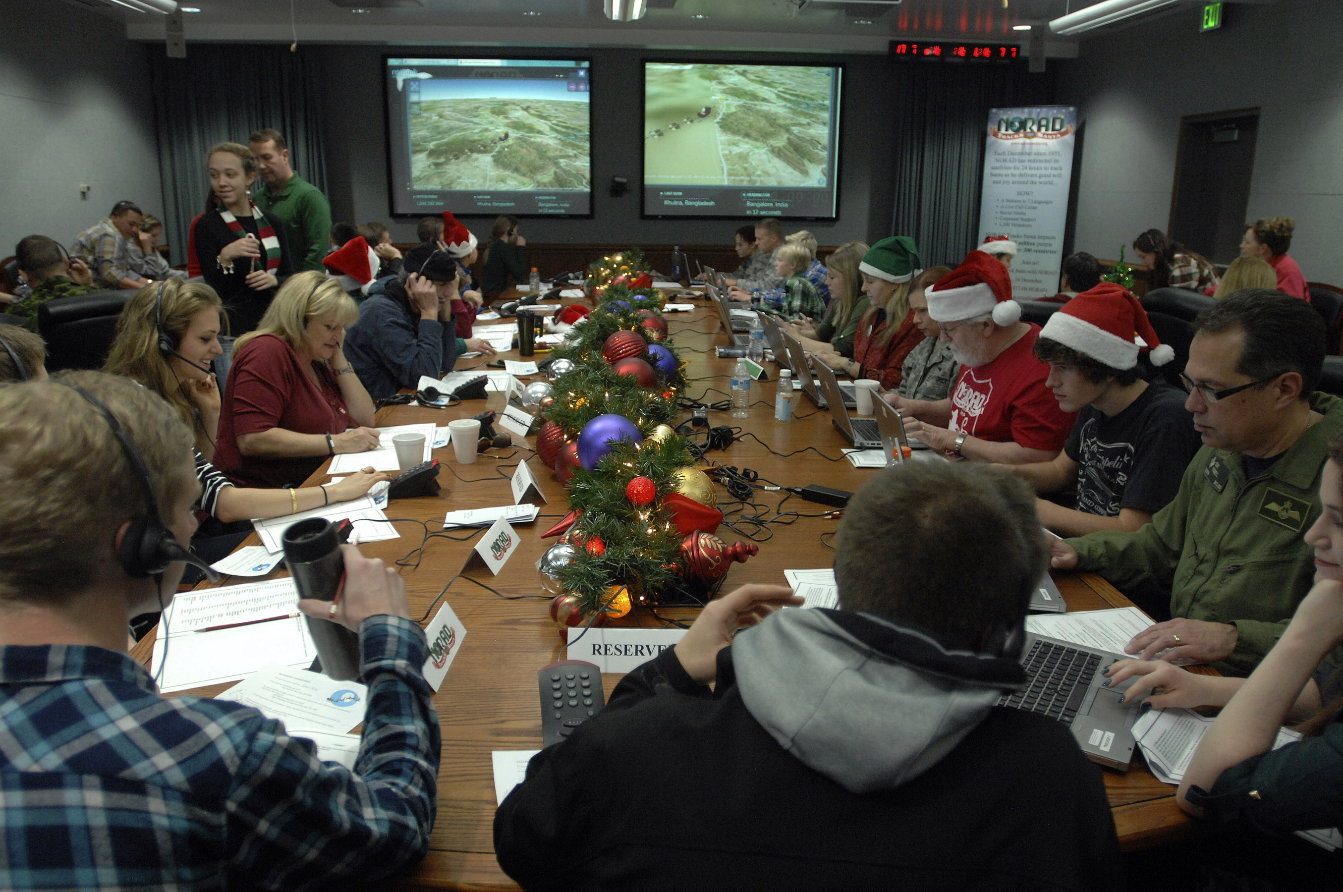 "Volunteers answer telephone calls and emails from parents and children around the world in the ""NORAD Tracks Santa"" operations center on Christmas Eve 2013. PHOTO: U.S. Air Force Master Sergeant Chuck Marsh."