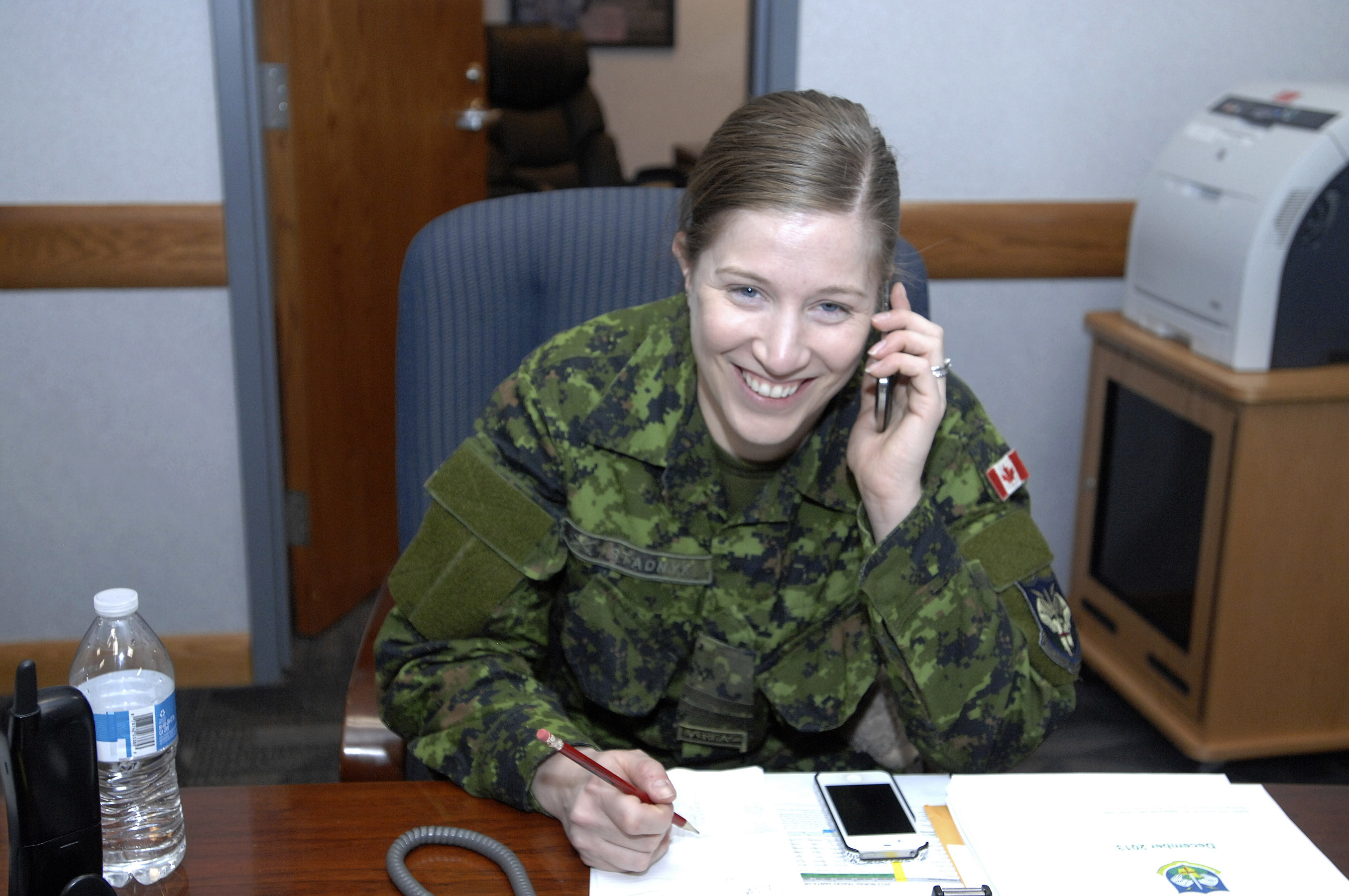 "Captain Jennifer Stadnyk, a member of the Canadian Armed Forces, answers a phone call in the ""NORAD Tracks Santa"" operations center at NORAD Headquarters in Colorado on Christmas Eve 2013. PHOTO: U.S. Air Force Master Sergeant Chuck Marsh."