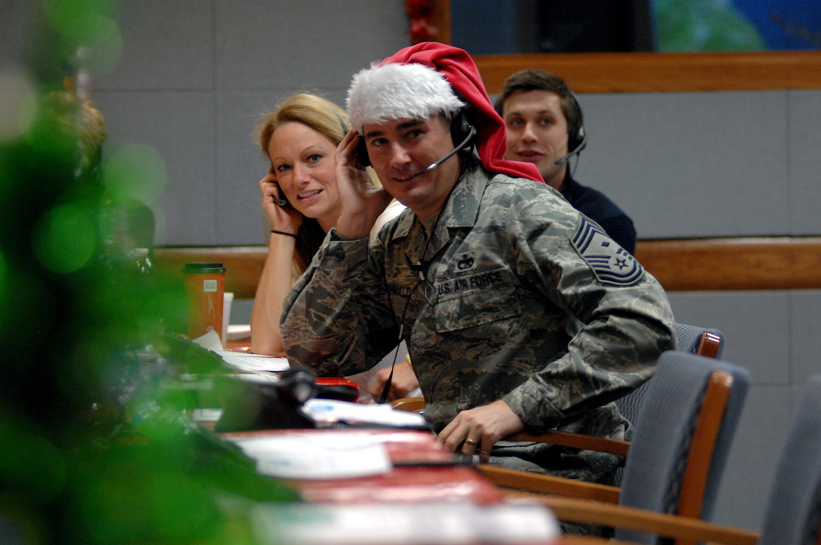 "Chief Master Sergeant Roderick Schwald, North American Aerospace Defense Command and U.S. Northern Command first sergeant, and other volunteers answer calls from children and parents around the world at the ""NORAD Tracks Santa"" operations center at Peterson Air Force Base, Colorado, on December 24, 2013. More than 1,200 volunteers – military and civilian – covered the 23 hours of tracking. PHOTO: U.S. Air Force Master Sergeant Chuck Marsh."