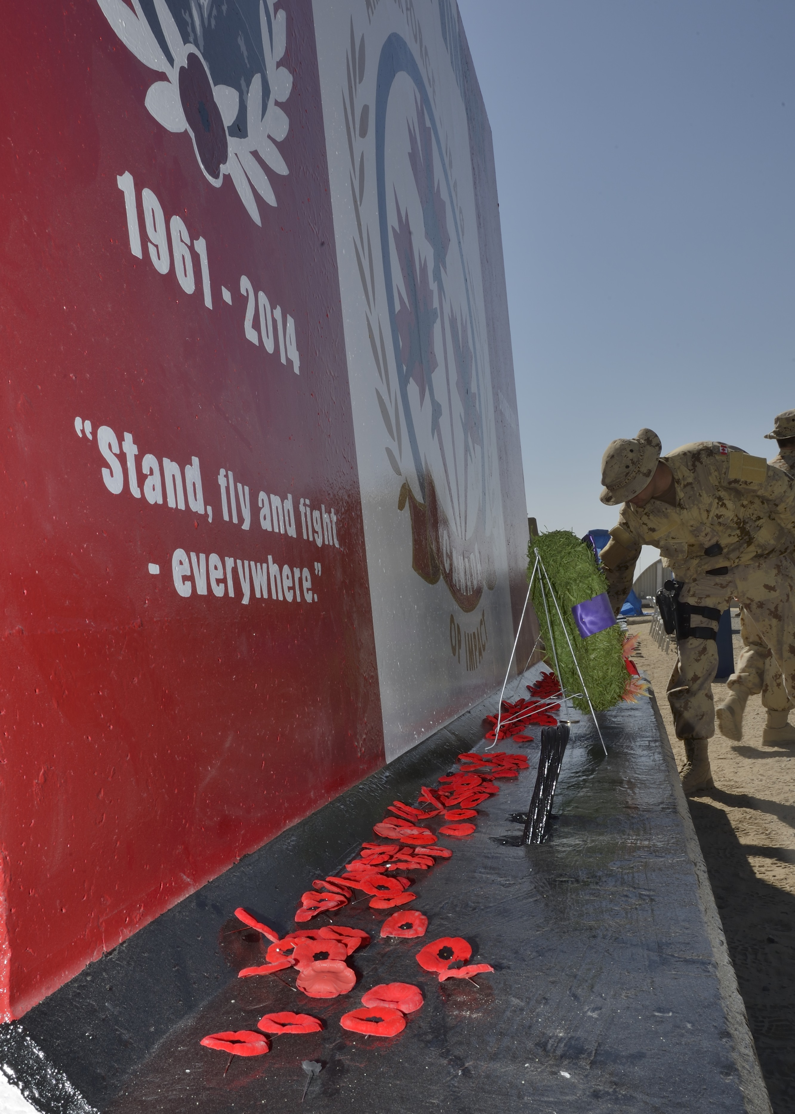 After the Remembrance Day ceremony on November 11, 2014, Canadian Armed Forces members deployed on Operation Impact in Kuwait place their poppies on the base of the new Camp Patrice Vincent commemorative wall. PHOTO: Canadian Forces Combat Camera, DND