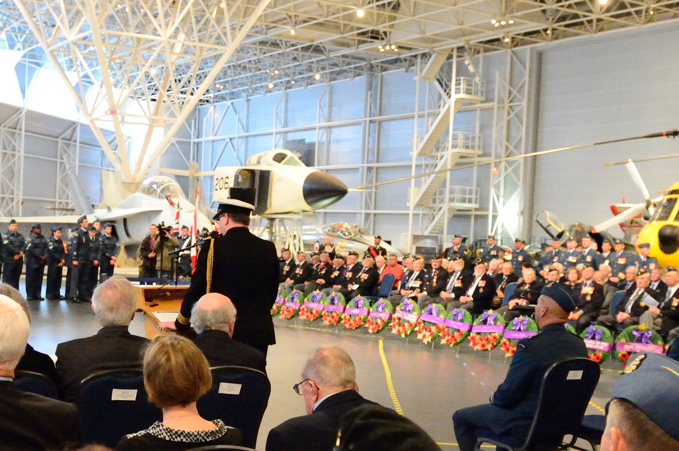 From their places of honour, Royal Canadian Air Force veterans (back right) listen as United Kingdom representative Commander Mike O'Sullivan speaks during the 2014 Battle of Britain Ceremony at the Canada Aviation and Space Museum in Ottawa, Ontario. PHOTO: Corporal Chase Miller