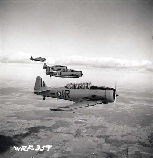 Four North American Harvards fly in formation near No. 2 Service Flying Training School at RCAF Uplands, Ontario, in July 1941. PHOTO: Nicholas Morant, PA-140659