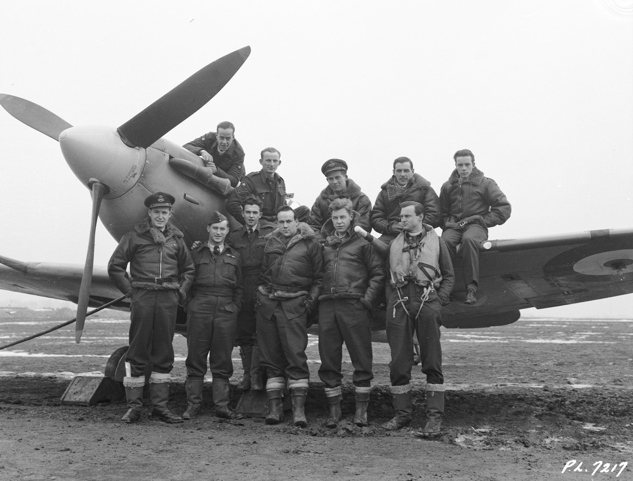 In RCAF squadrons based in Great Britain, most Spitfire aircrew were products of the British Commonwealth Air Training Plan in Canada. This photo, taken February 12, 1942, shows eleven members of 403 Squadron. Front, left: Pilot Officer J.N. Cawsey, Calgary, Alberta; Pilot Officer J.T. Parr, Barrie, Ontario; Flight Sergeant E.A. Crist, Wallaceburg, Ontario; Sergeant D.D. Connell, Hamilton, Ontario; Sergeant J.H. Oliver, Toronto, Ontario; and Sergeant H.R. Olmsted, Ottawa, Ontario. Back, left: Flight Sergeant J.B. Rainville, St. Johns, Quebec; Flight Sergeant A.H. McDonald, Fleming, Saskatchewan; Pilot Officer D.S. Hurst, Winnipeg, Manitoba; Flight Sergeant F.H. Belcher, Roblin, Manitoba; and Flight Sergeant G.A.J. Ryckman, London, Ontario. PHOTO: DND Archives,
