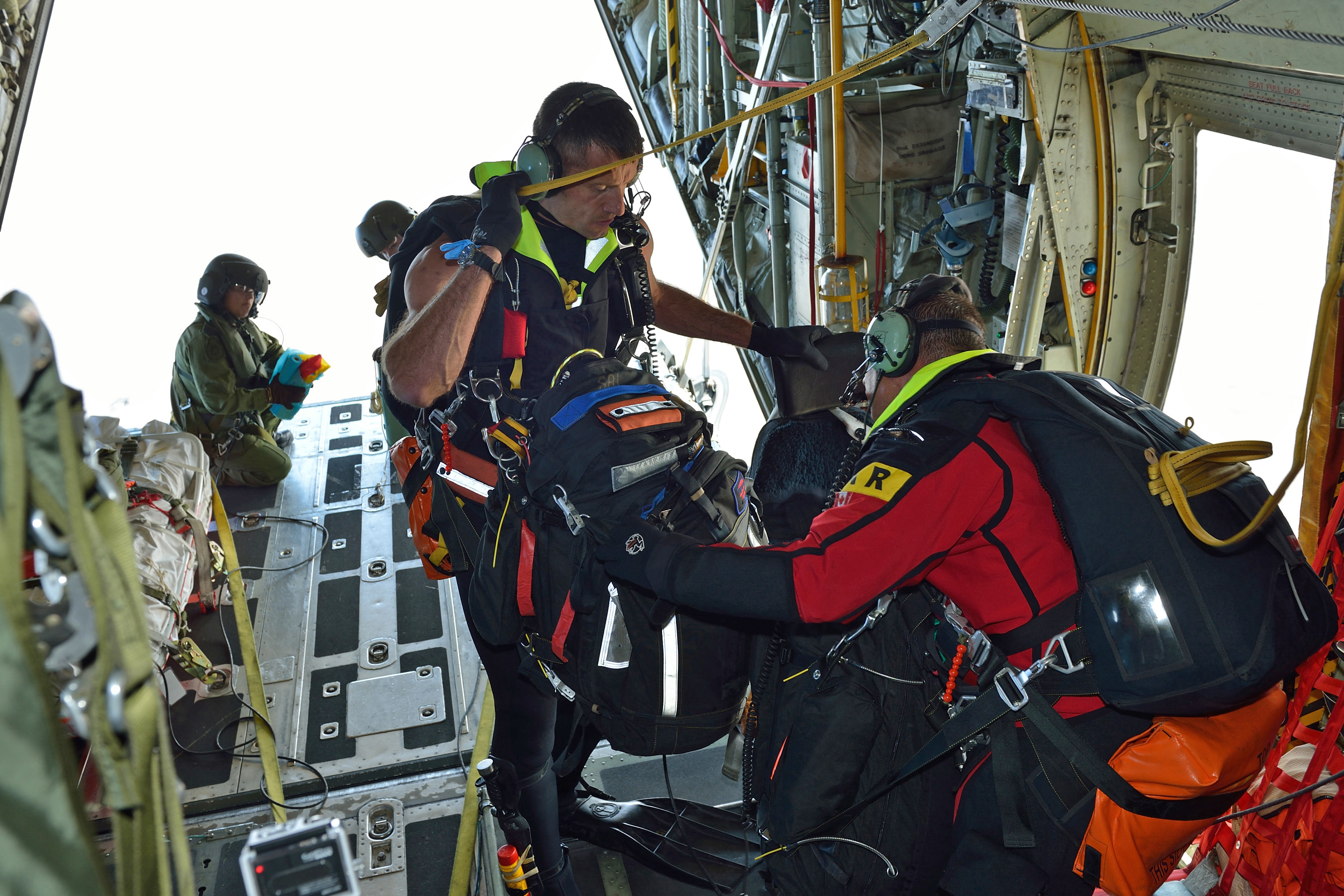Sergeant Mark Salesse (centre) and Master Corporal Danny Dicerni (right), search and rescue technicians with 435 Transport and Rescue Squadron in Winnipeg, Manitoba, prepare their equipment to jump from a CC-130 Hercules aircraft to a simulated vessel in distress, while Sergeant Nathalie Verret readies streamers during the National Search and Rescue Exercise held in Gimli, Manitoba, on September 17, 2013. PHOTO: Sergeant Bill McLeod