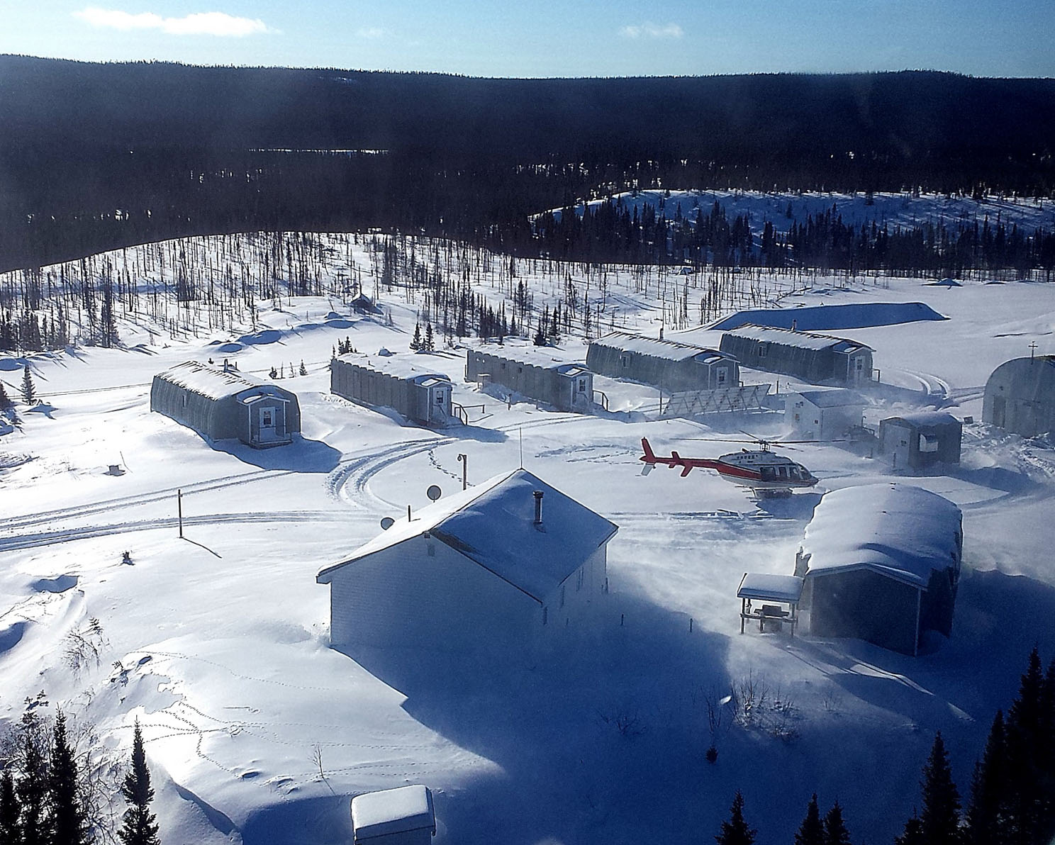 A helicopter stirs up snow in the centre of the camp. PHOTO: DND
