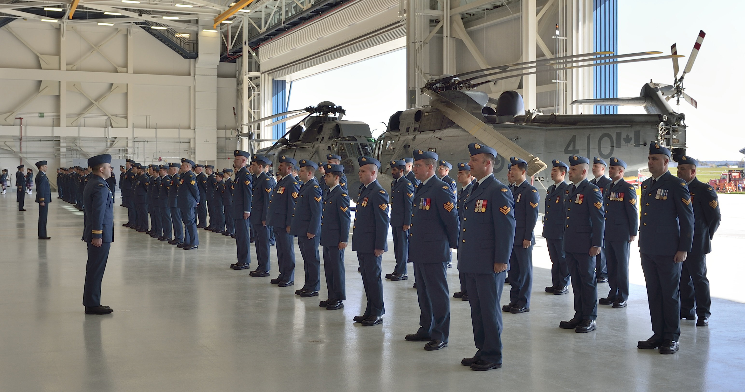 Members of 443 Maritime Helicopter Squadron stand on parade during a ceremony to mark the official opening and naming of their new hangar facility at the Victoria International Airport on April 9, 2015. The ceremony included a parade to celebrate the consecration of a new squadron Colour and the unveiling of the hangar's name.