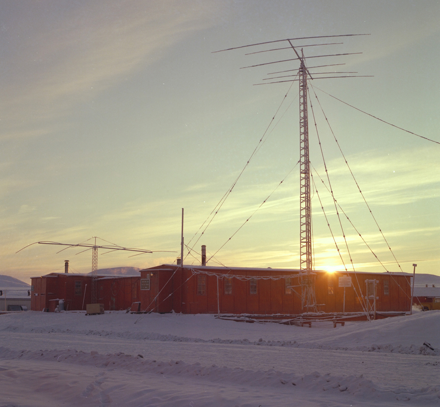 The sun goes down behind the new transmitter site at Canadian Forces Station Alert, Ellesmere Island, on October 9, 1976, leaving the world's northernmost permanent settlement heading into extended periods of darkness with no sunlight at all between mid-October and late February. PHOTO: DND
