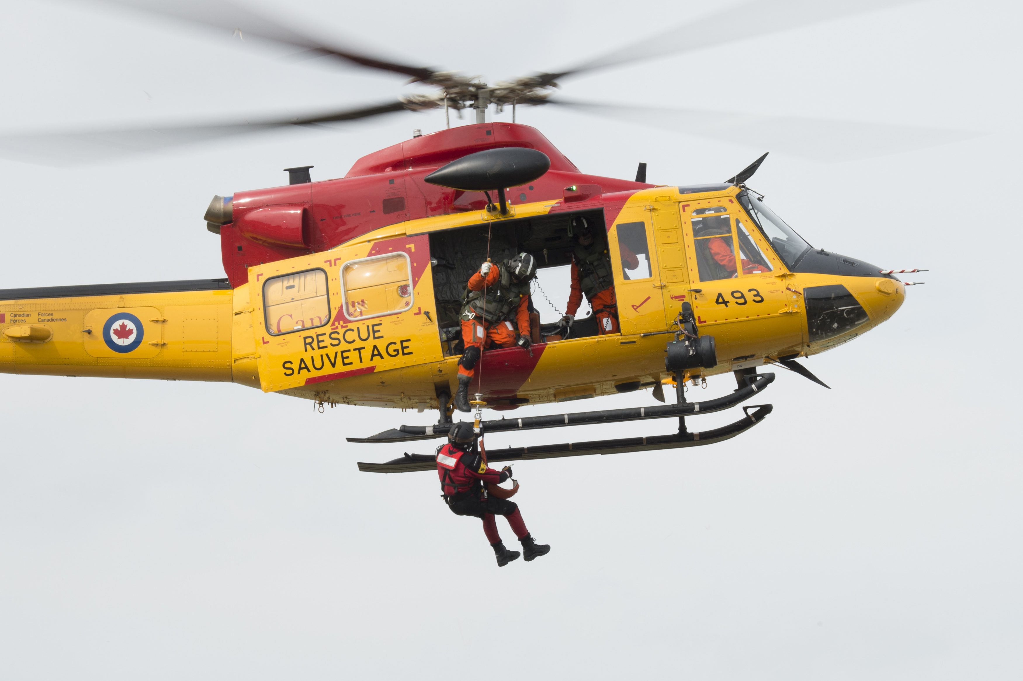 A flight engineer lowers a search and rescue technician from 424 Transport and Rescue Squadron, located at 8 Wing Trenton, Ontario, to the ground from a Griffon helicopter during TIGEREX 2015 at the Lake Simcoe Airport on May 5, 2015.