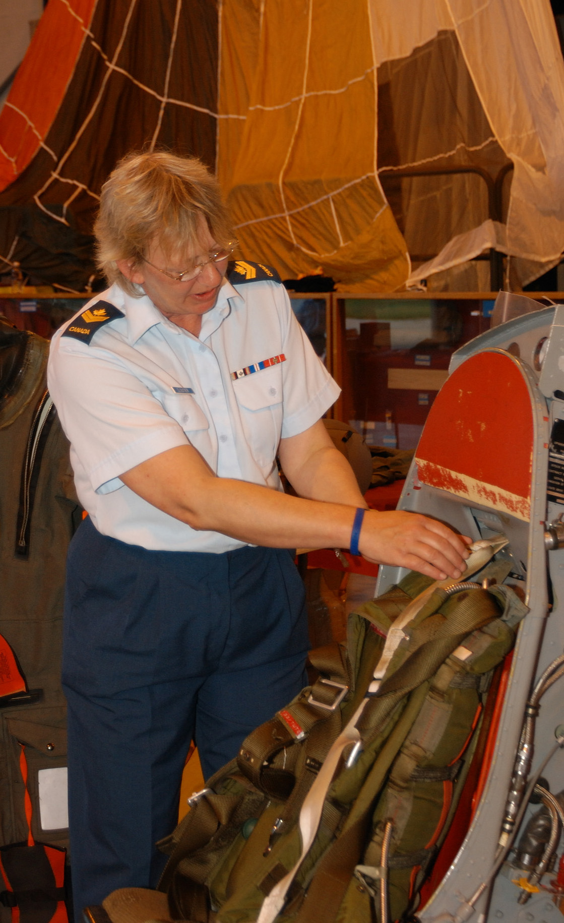 Master Corporal Bridgitte Cloutier, an aviation technician at 16 Wing Borden, Ontario, adjusts the straps of an ejection seat in the aviation life support equipment display on Armed Forces Day in June 2008. PHOTO: Sergeant Kev Parle