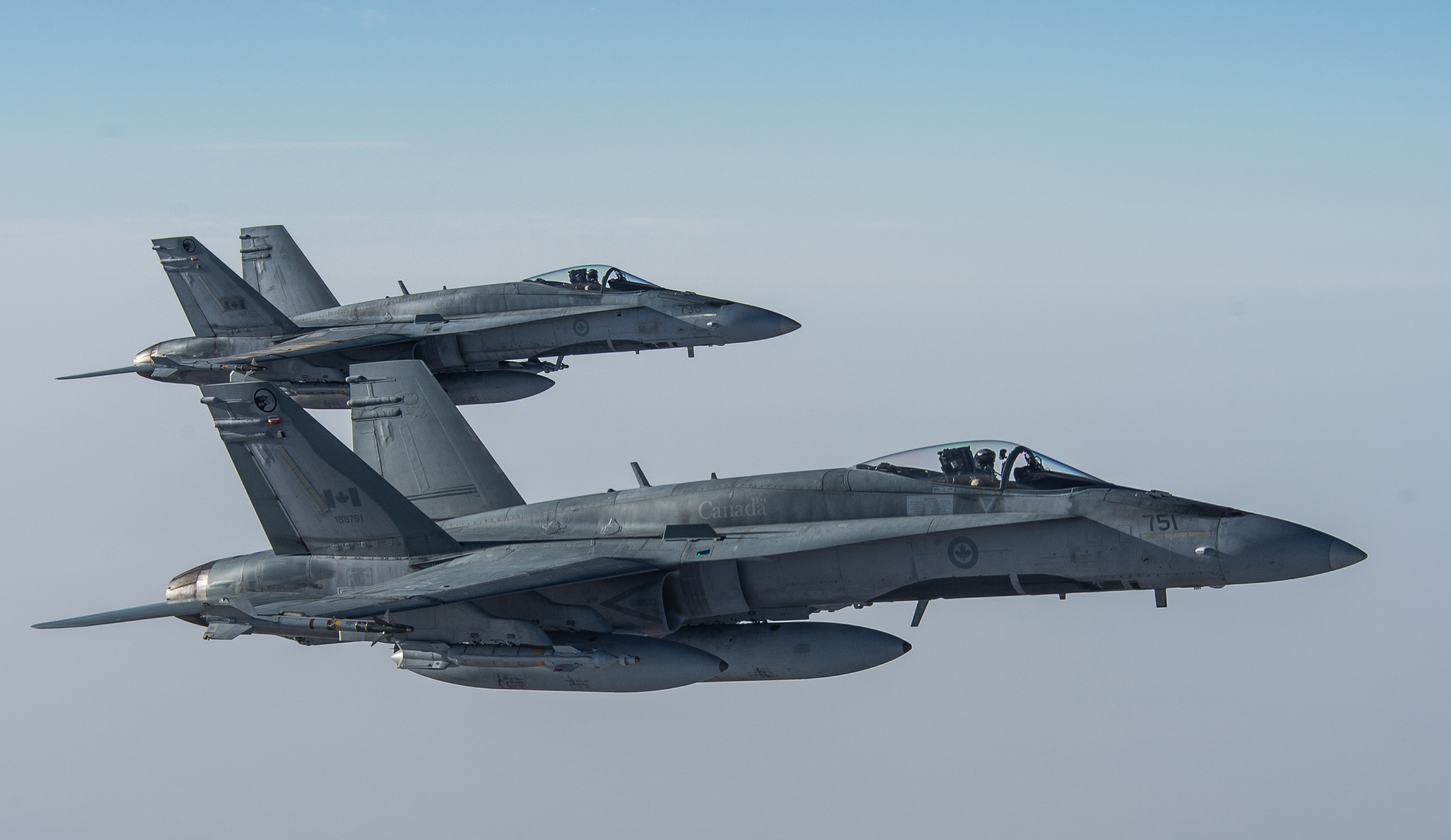 Two CF-188 Hornet fighters prepare to resume their activities after being refueled by a CC-150T Polaris on February 4, 2015 during Operation Impact. PHOTO: Canadian Forces Combat Camera, DND