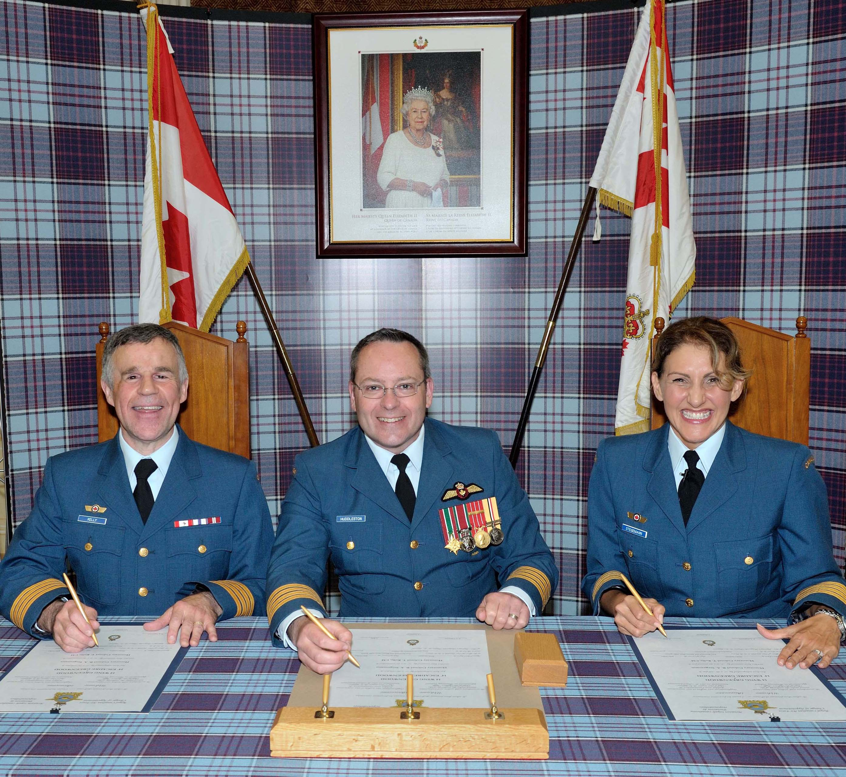 Honorary Colonel Terry Kelly (left), 14 Wing Greenwood's new honorary colonel, Colonel Iain Huddleston (centre), commander of 14 Wing, and Honorary Colonel Barb Stegemann, outgoing honorary colonel, sign the change of appointment documents on July 6, 2015