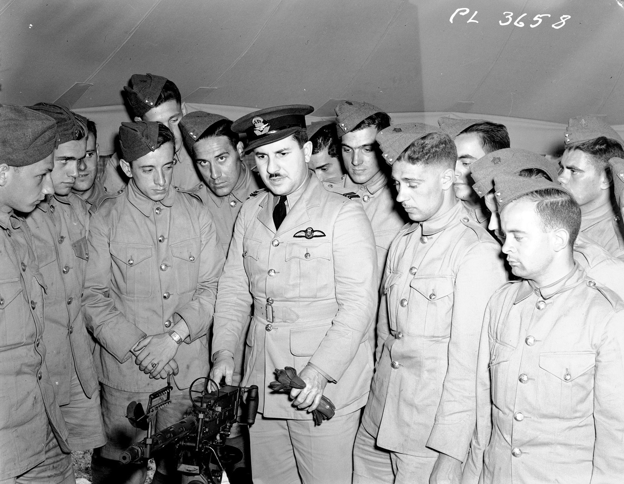 Squadron Leader Jean-Paul Desloges explains the workings of a Browning machine gun to trainees at No. 3 Air Training Corps in Montreal, Quebec, on June 11, 1941. PHOTO: DND
