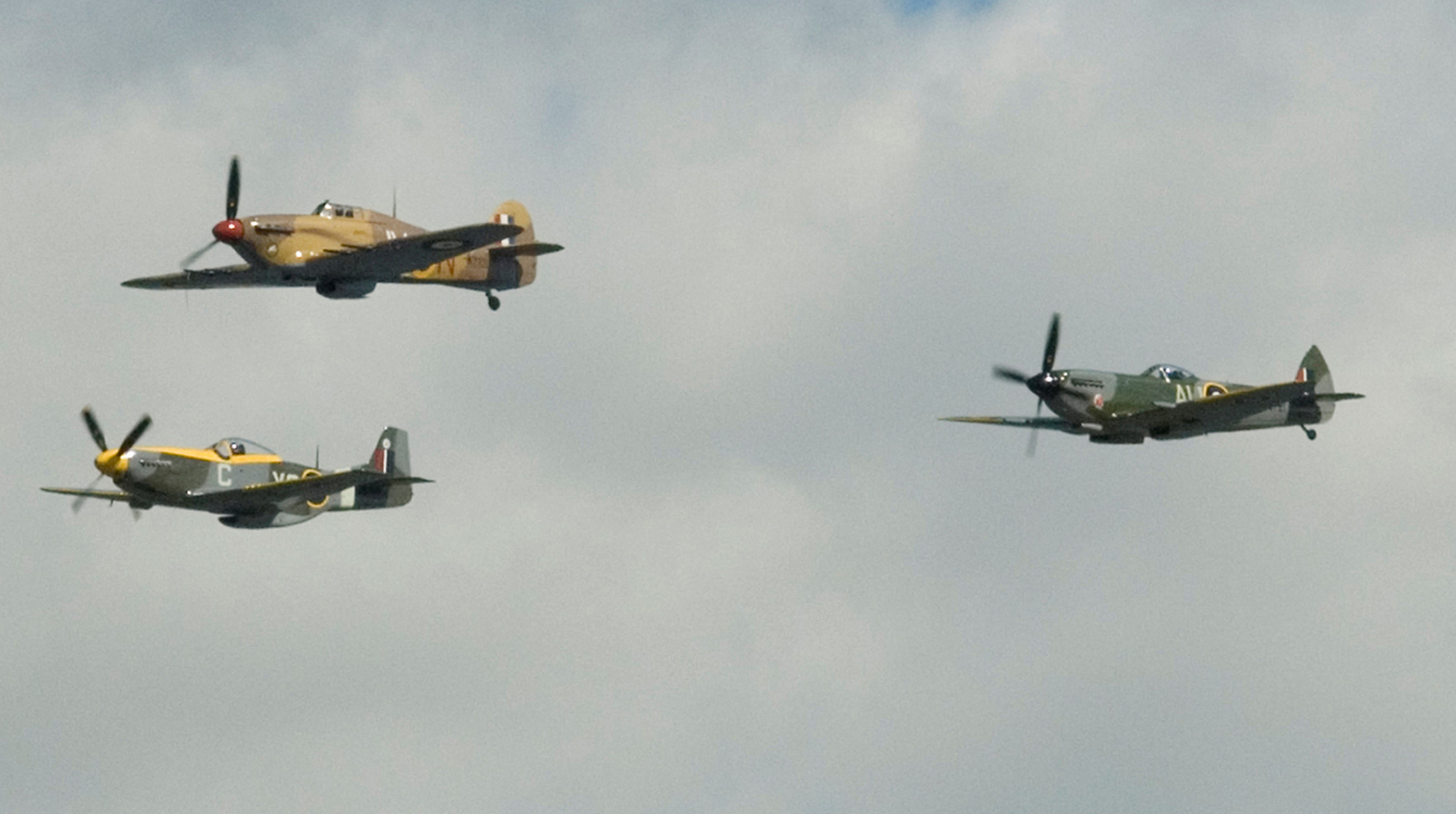 Although they flew somewhat different versions of these iconic aircraft, Canadians operated Mustang (left), Hurricane and Spitfire (right) aircraft in the skies over Dieppe on August 19, 1942. These aircraft, photographed in 2007, belong to Vintage Wings of Canada.  PHOTO: Cory Hunter, IS2007-9214