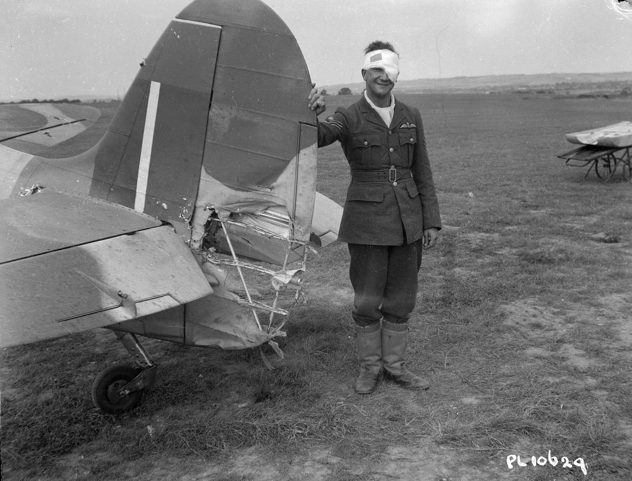 A man, who is wearing a military uniform and has a white bandage wrapped around his head, stands beside a damaged aircraft.