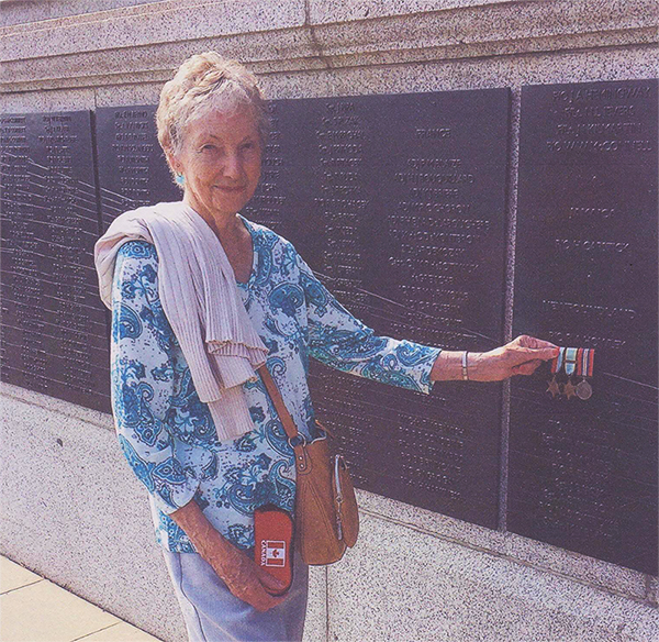 Pilot Officer Dick Howley's younger sister, Tina Howley Harney, displays her brother's medals under his name on the Battle of Britain London Monument, in London, England, in September 2014. PHOTO: Courtesy of Tina Harney