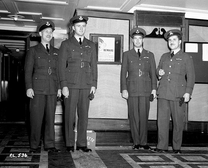 "On the eve of their departure from Canada for Europe in early June 1940, Royal Canadian Air Force No. 1 Squadron Flying Officers Hartland de Montarville Molson (left) and Paul Brooks Pitcher, both of Montreal, Quebec; Pilot Officer Arthur Deane Nesbitt, also of Montreal; and Flying Officer Jean-Paul Joseph Desloges of Ottawa, Ontario, stand around a sign that is in frequent evidence in zones where the public is warned to refrain from the discussion of troop movements. The sign, illustrated with a caricature of a ""listening"" Adolph Hitler, reads, ""Whether alone or in a crowd, Never write or say aloud What you're loading, whence you hail, Where you're bound for, when you sail. Above all, never give away the movements of H.M. Ships."" PHOTO: DND"