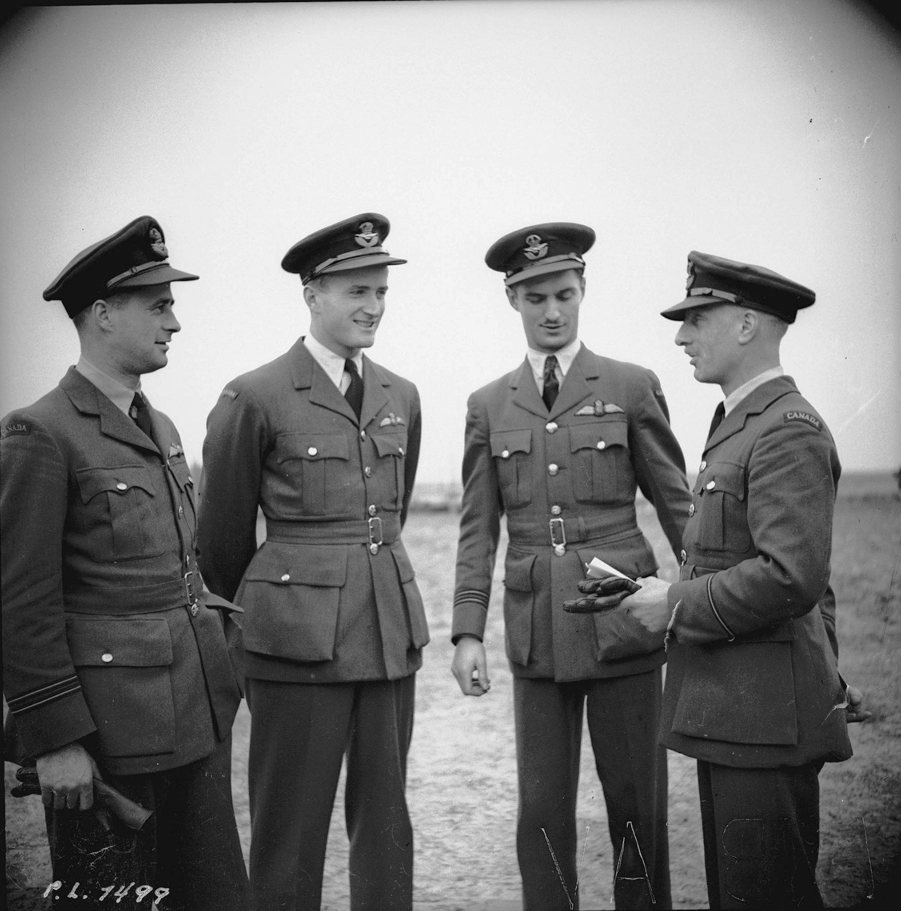 417 Canadian Squadron members Flight Lieutenant F. B. Foster (left) and Squadron Leader Paul Brooks Pitcher, from Montreal, Quebec; and Flight Lieutenant W.H. Pentland, from Calgary, Alberta, are briefed by Flying Officer J.M. Rutherford (adjutant), also from Montreal, on April 16, 1942. PHOTO: DND
