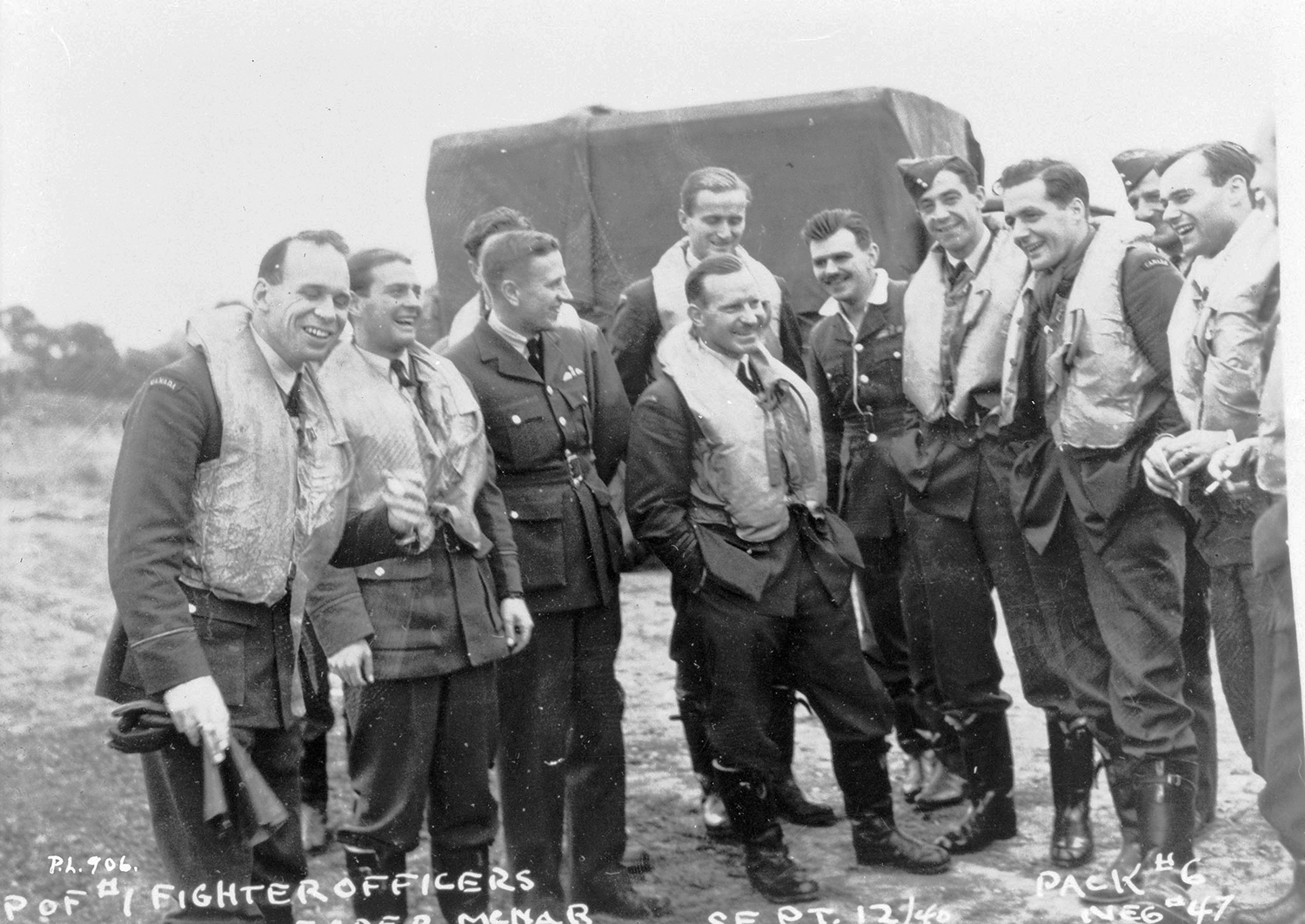 Squadron Leader Ernest McNab and some of his pilots pose for a photo and a laugh September 12, 1940, during the Battle of Britain: (left to right) Flying Officer William P. Sprenger, Flying Officer Otto John Peterson, Flight Lieutenant W.R. Pollock (adjudant), Flying Officer Paul Brooks Pitcher, Squadron Leader McNab, Flying Officer Peter William Lochnan, Flight Lieutenant Edwin Michael Reyno, Flying Officer Eric Walter Beardmore, Flying Officer S.T. Blaiklock (intelligence officer) and Flying Officer Robert William Norris. PHOTO: Courtesy Library and Archives of Canada