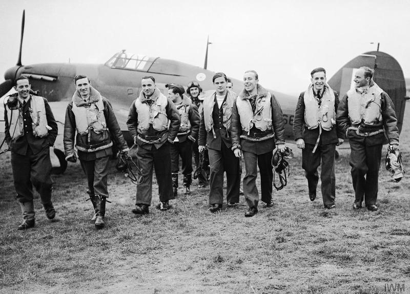 A group of pilots of No. 303 Polish Fighter Squadron walk towards the camera from a Hawker Hurricane after returning from a fighter sortie on October 24, 1940.