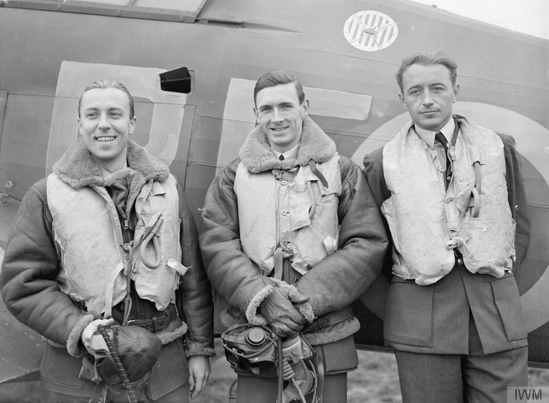 Flying Officer Zdzisław Henneberg, Flight Lieutenant John A. Kent and Flying Officer Marian Pisarek, all from No. 303 (Polish) Fighter Squadron, stand by a squadron Hurricane at RAF Leconfield on October 24, 1940. Note the squadron's badge over their heads. PHOTO: © Imperial War Museum (CH 1535)